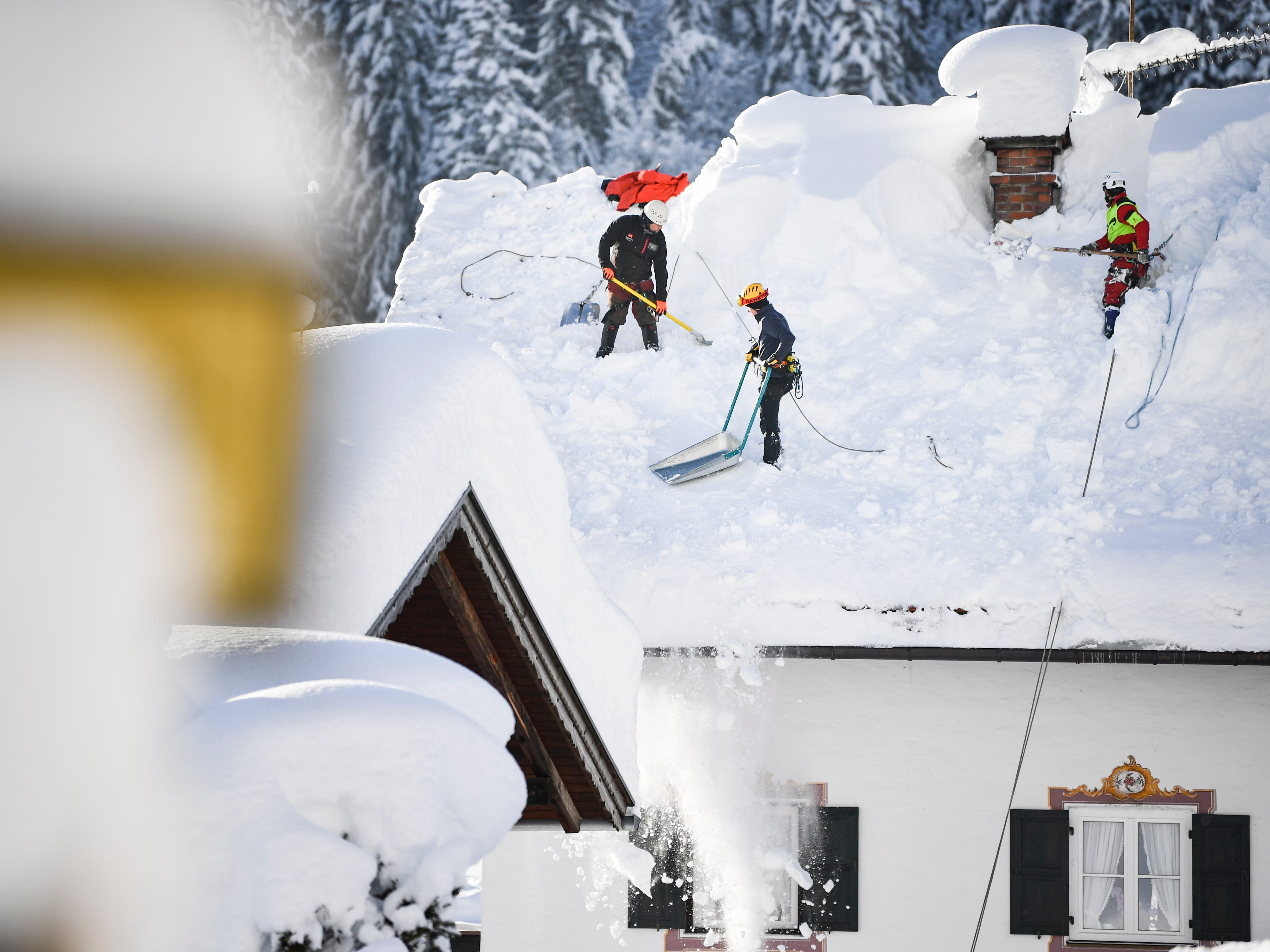 Workers clear a roof in Gerold, Germany, Jan. 11, 2019.