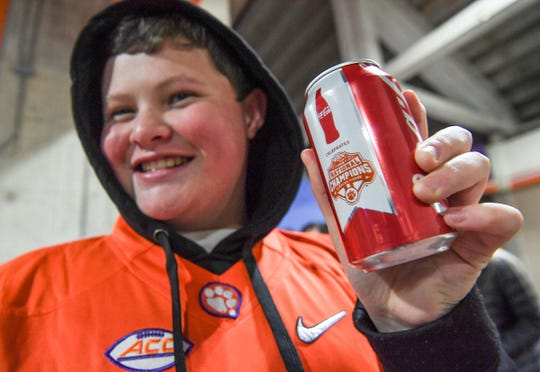 James Dean of Clinton, S.C. holds a commemorative Coke can he got, for the first 2,400 fans, during the National Championship parade for the Clemson Tigers football team in Clemson Saturday, January 12, 2019. They are expected to release the cans in stores soon, and bottles in late July.