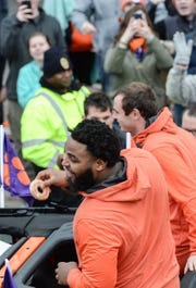 Clemson defensive lineman Christian Wilkins and wide receiver Hunter Renfrow toss donuts to fans during the National Championship parade for the Clemson Tigers football team in Clemson Saturday, January 12, 2019.