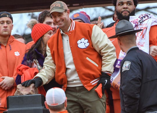 Clemson Head Coach Dabo Swinney rubs Howard's Rock during the National Championship parade for the Clemson Tigers football team in Clemson Saturday, January 12, 2019.