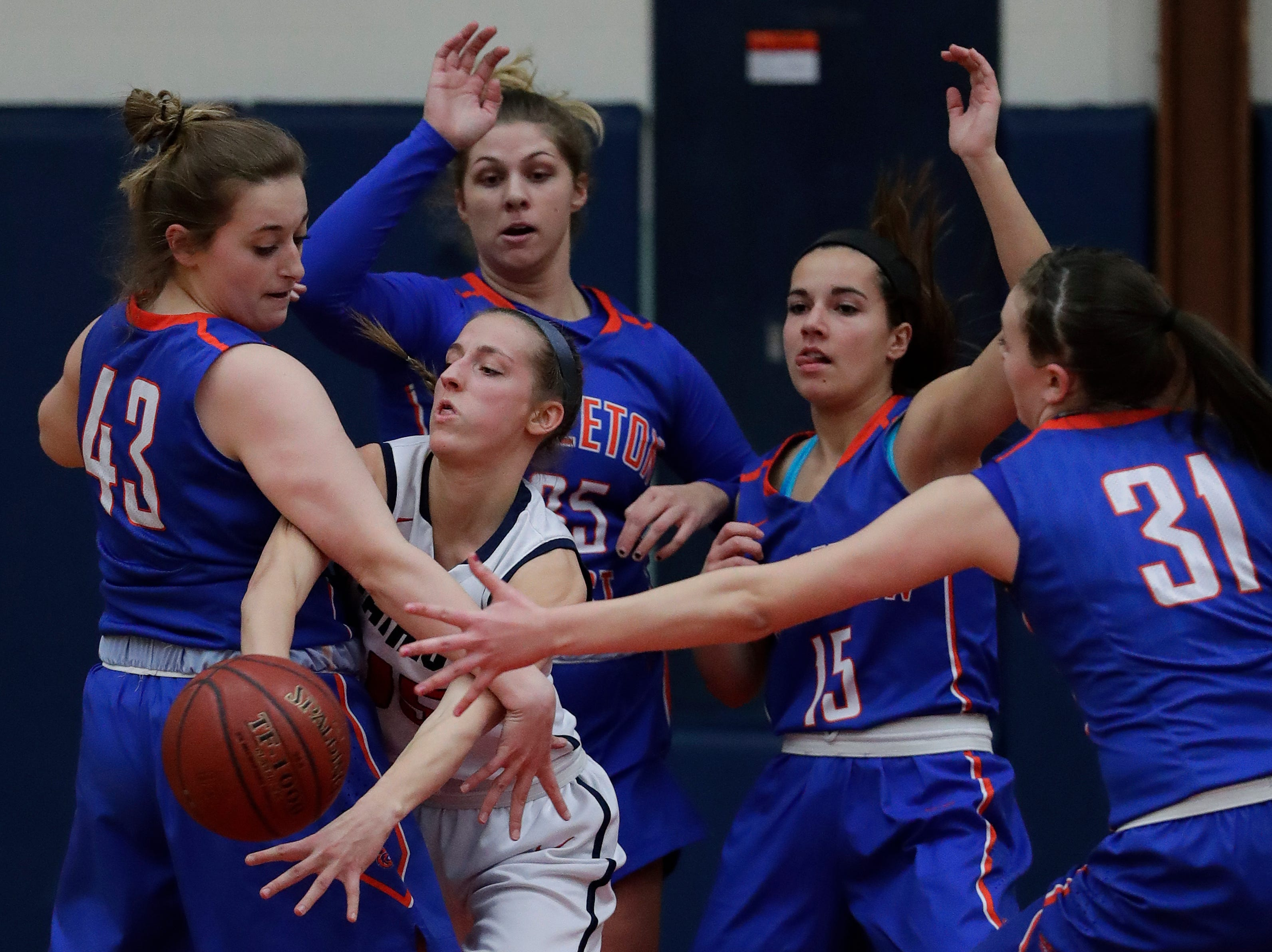 Appleton East High School's Meghan Borowski (15) is under heavy defensive pressure from Appleton West High School's Jenna Hoffman (43), Sydney Gehl (35), Addie Pauling (15) and Christy Fortune (31) during their girls basketball game Friday, January 11, 2019, at Appleton East High School in Appleton, Wis. 
