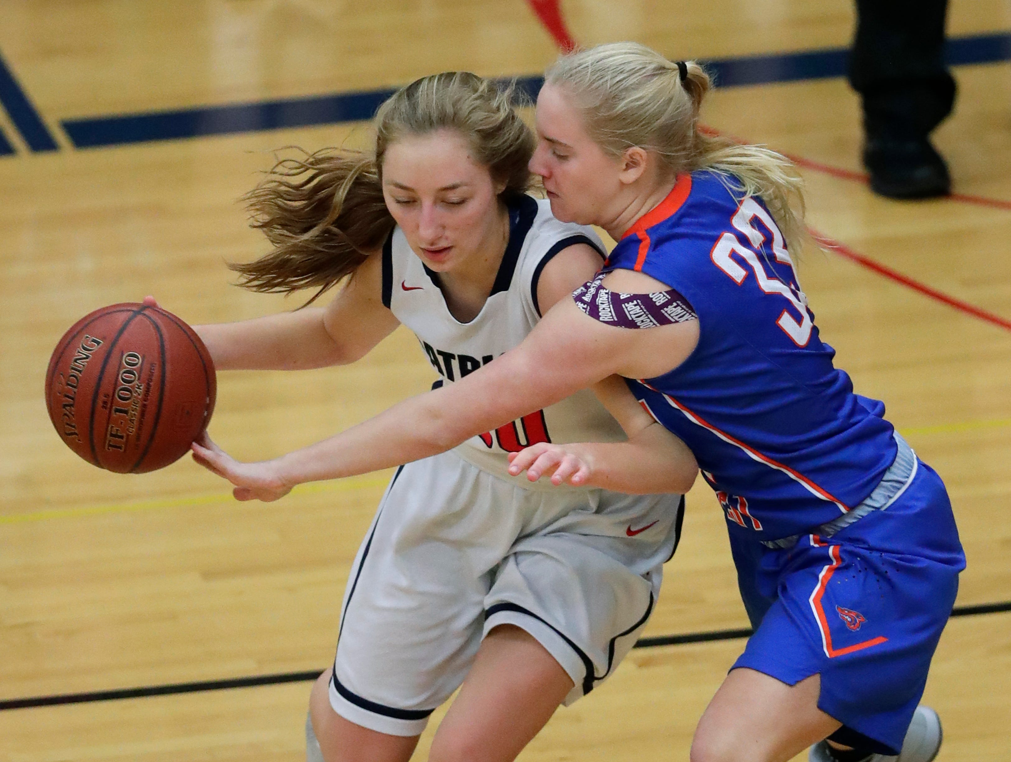 Appleton West High School's McKayla Knoebel (33) knocks the ball away from Appleton East High School's Cameron Neubauer (10) during their girls basketball game Friday, January 11, 2019, at Appleton East High School in Appleton, Wis. 