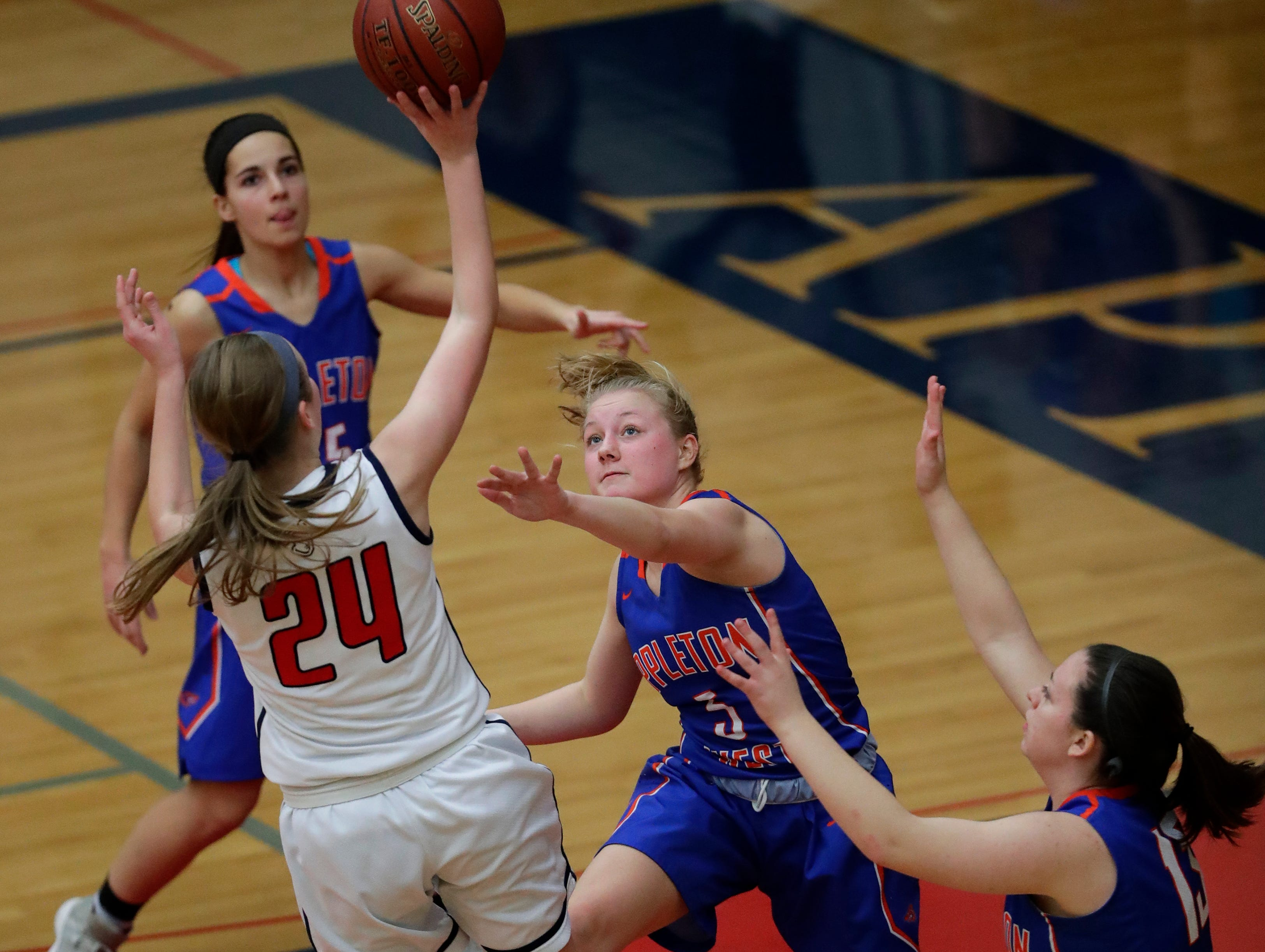 Appleton East High School's Delaney Clark (24) puts up a shot against Appleton West High School's Bree Workman (5) during their girls basketball game Friday, January 11, 2019, at Appleton East High School in Appleton, Wis. 