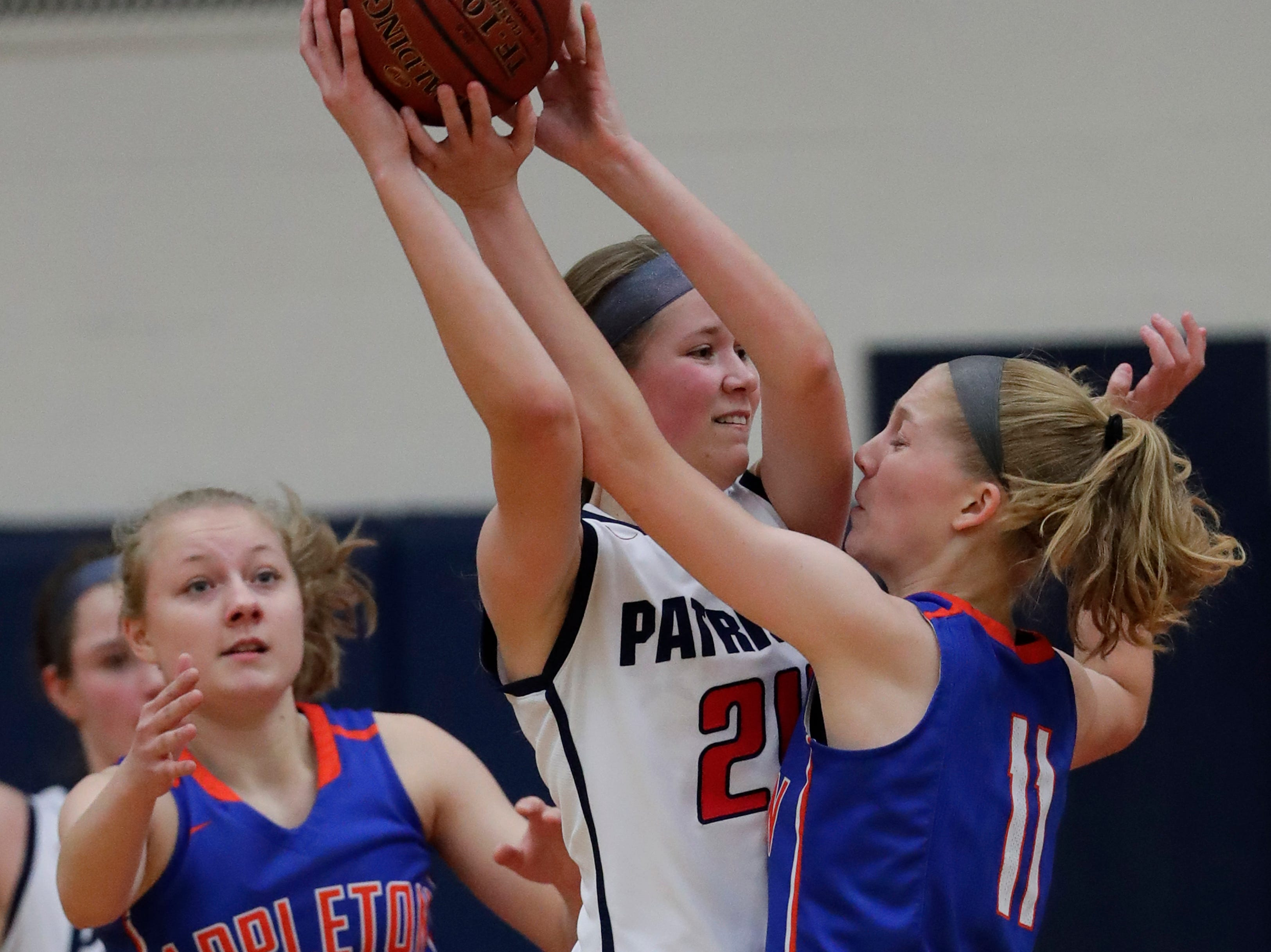Appleton East High School's Delaney Clark (24) tries to pass the ball against Appleton West High School's Bree Workman (5) and Jamie Winsted (11) during their girls basketball game Friday, January 11, 2019, at Appleton East High School in Appleton, Wis. 