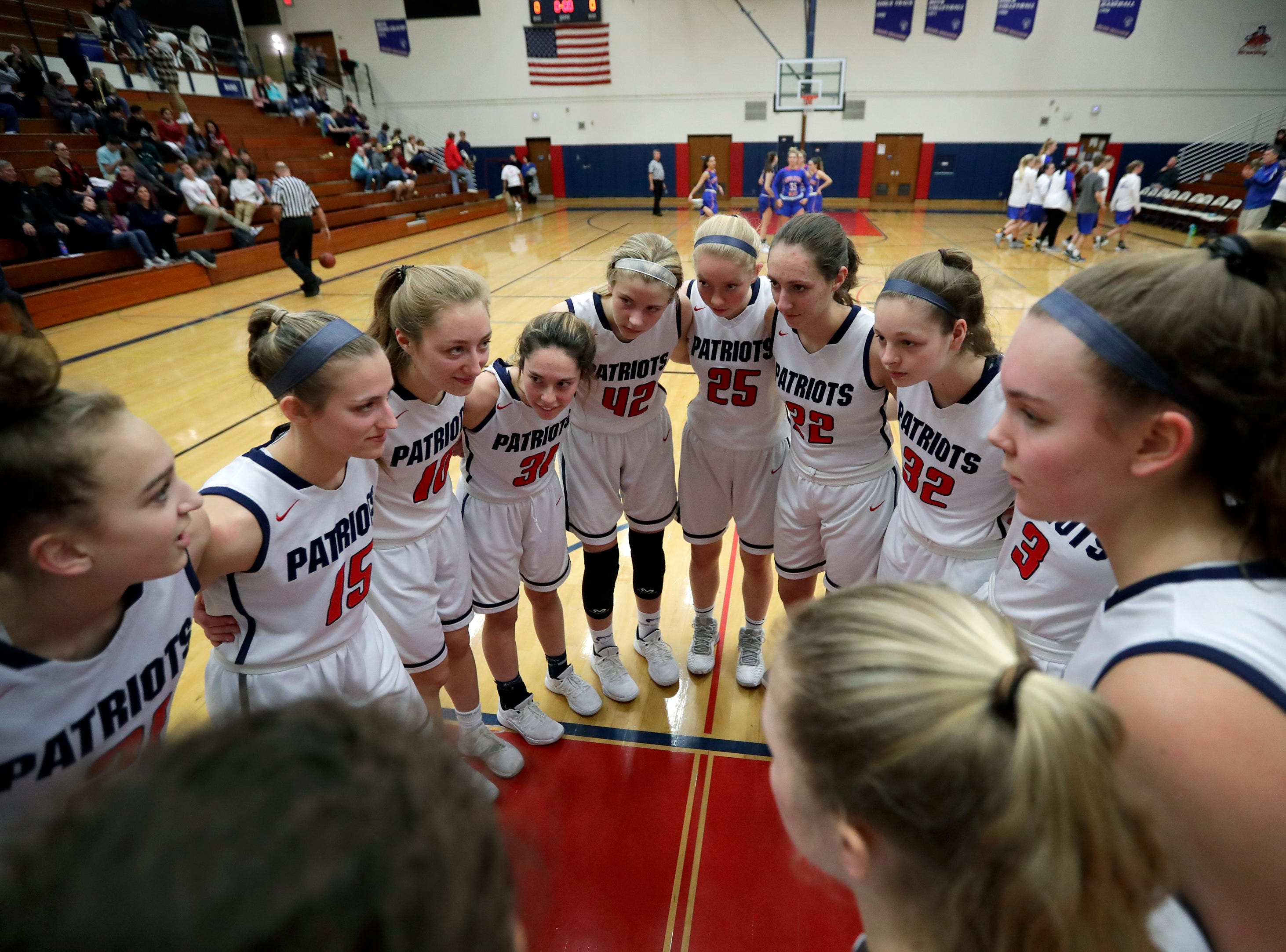 Appleton East High School's players gather arm in arm moments before playing against Appleton West High School during their girls basketball game Friday, January 11, 2019, at Appleton East High School in Appleton, Wis. 
