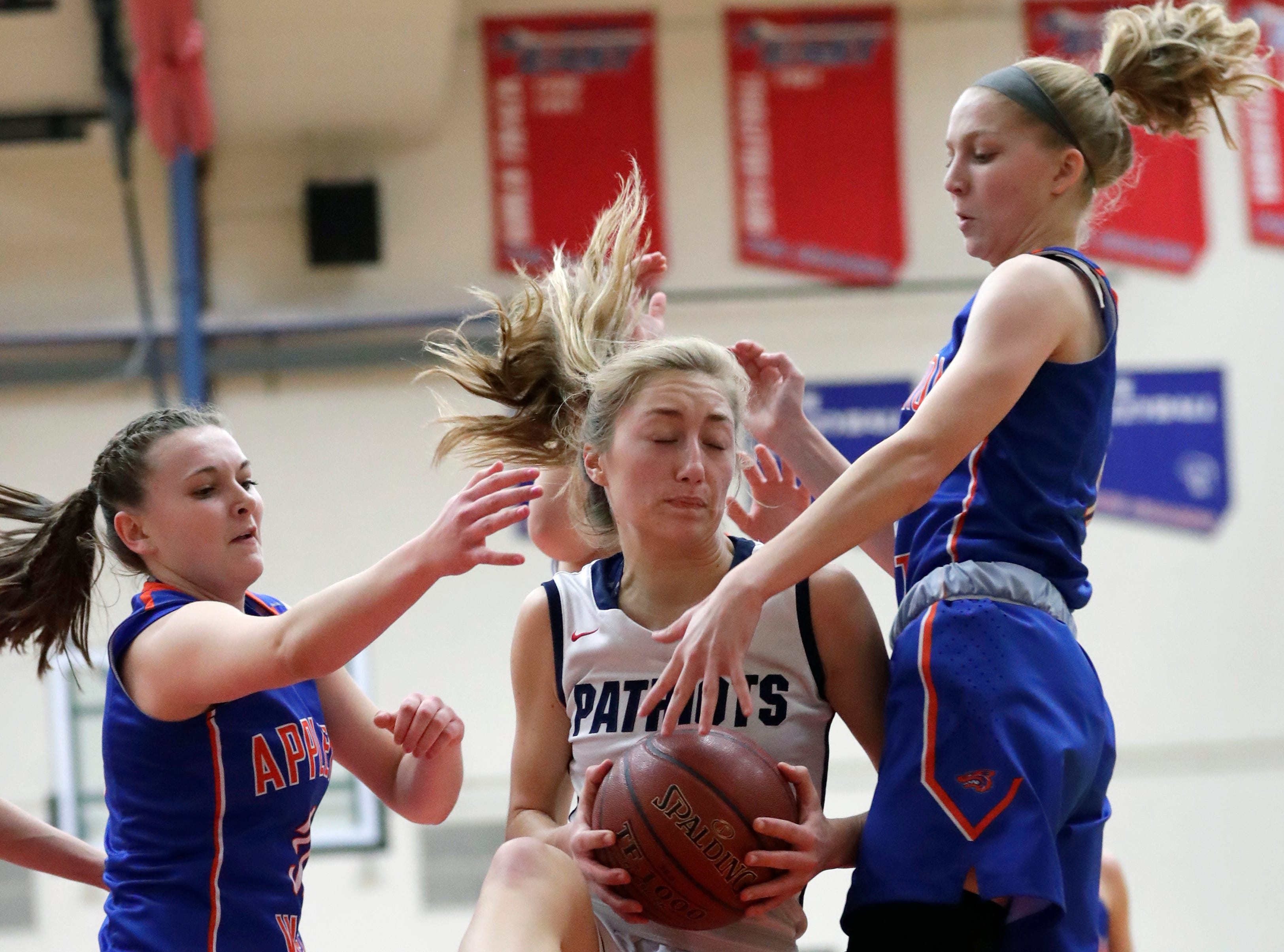 Appleton East High School's Cameron Neubauer, center, drives to the basket against Appleton West High School's Christy Fortune, left, and Jamie Winsted, right, during their girls basketball game Friday, January 11, 2019, at Appleton East High School in Appleton, Wis. 
