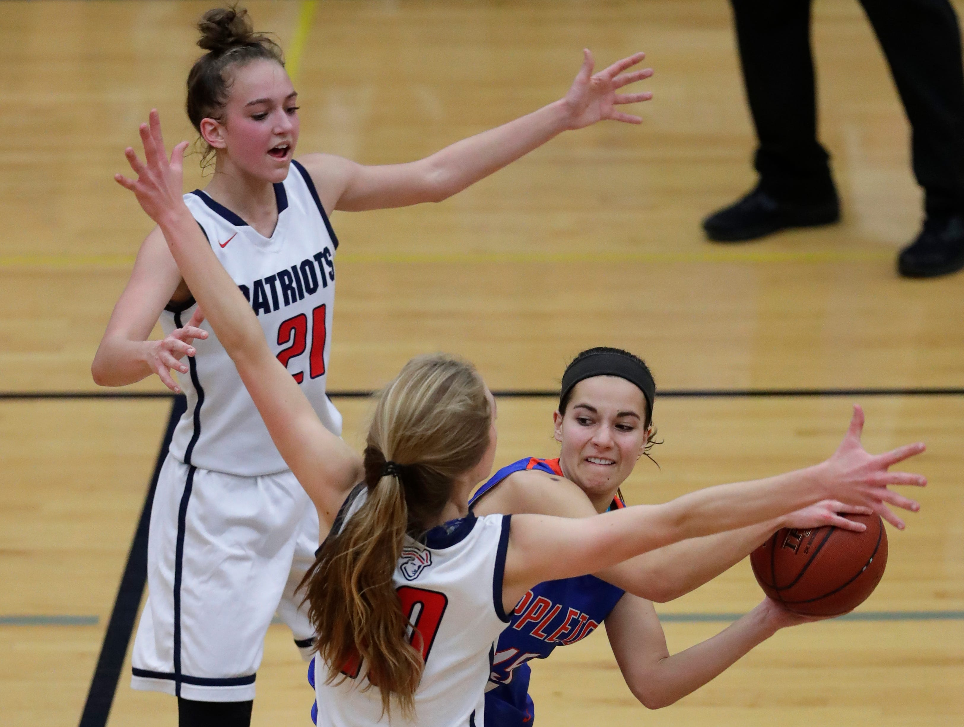 Appleton East High School's Cameron Neubauer (1) and Emily LaChapell (21) defend against Appleton West High School's Addie Pauling (15) during their girls basketball game Friday, January 11, 2019, at Appleton East High School in Appleton, Wis. 