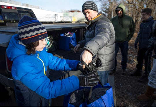 Chris Lawler of Chester County, PA. and his son Jake, 11, unload supplies for the homeless. Members of the community come out to offer support for homeless in the area. They delivered sleeping bags and other supplies to help them deal with cold weather. 