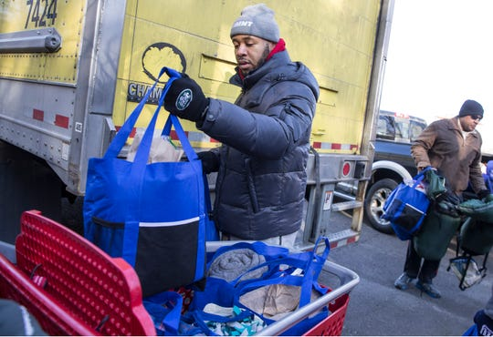 Robert Leaks of Howell unloads supplies for the homeless. Members of the community come out to offer support for homeless in the area. They delivered sleeping bags and other supplies to help them deal with cold weather. 