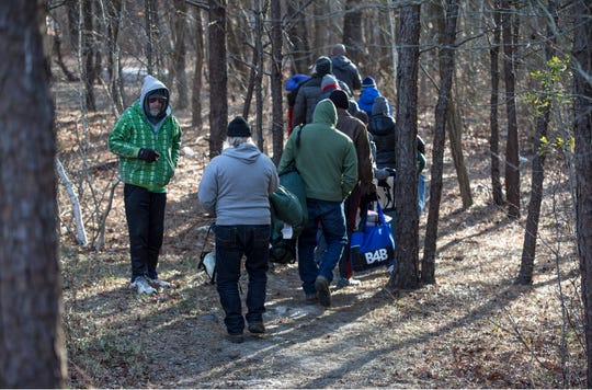 Volunteers hike back to the encampment with supplies for the homeless. Members of the community come out to offer support for homeless in the area. They delivered sleeping bags and other supplies to help them deal with cold weather. 
