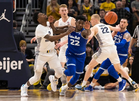 Seton Hall Pirates guard Myles Cale (22) and Marquette Golden Eagles guard Markus Howard (0) chase the loose ball