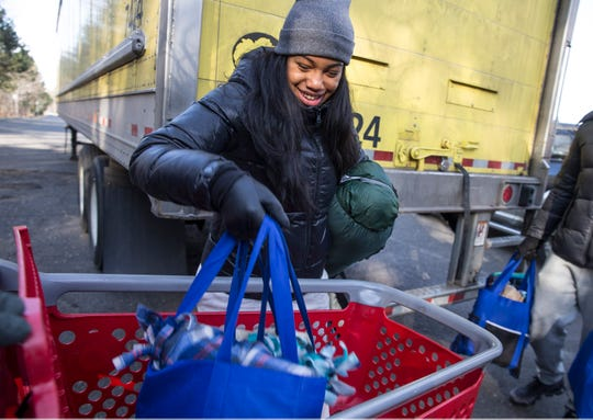 Jasmine Austin of Jackson unloads supplies for the homeless. Members of the community come out to offer support for homeless in the area. They delivered sleeping bags and other supplies to help them deal with cold weather. 