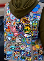 Patches adorn Morgan Medlin's Girl Scout vest Saturday as she assists families picking up their Girl Scout cookie orders.