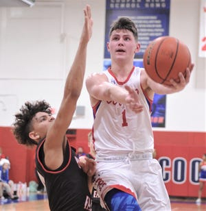 Cooper's Deven Bailey (1) drives to the basket as Wichita Falls High's Leon Dennis defends. Cooper beat the Coyotes 64-49 in the District 4-5A opener Friday, Jan. 11, 2019, at Cougar Gym.