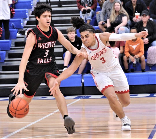 Cooper's Noah Garcia, right, tries to knock the ball away from Wichita Falls High's Austin Dishman. Cooper beat the Coyotes 64-49 in the District 4-5A opener Friday, Jan. 11, 2019, at Cougar Gym.