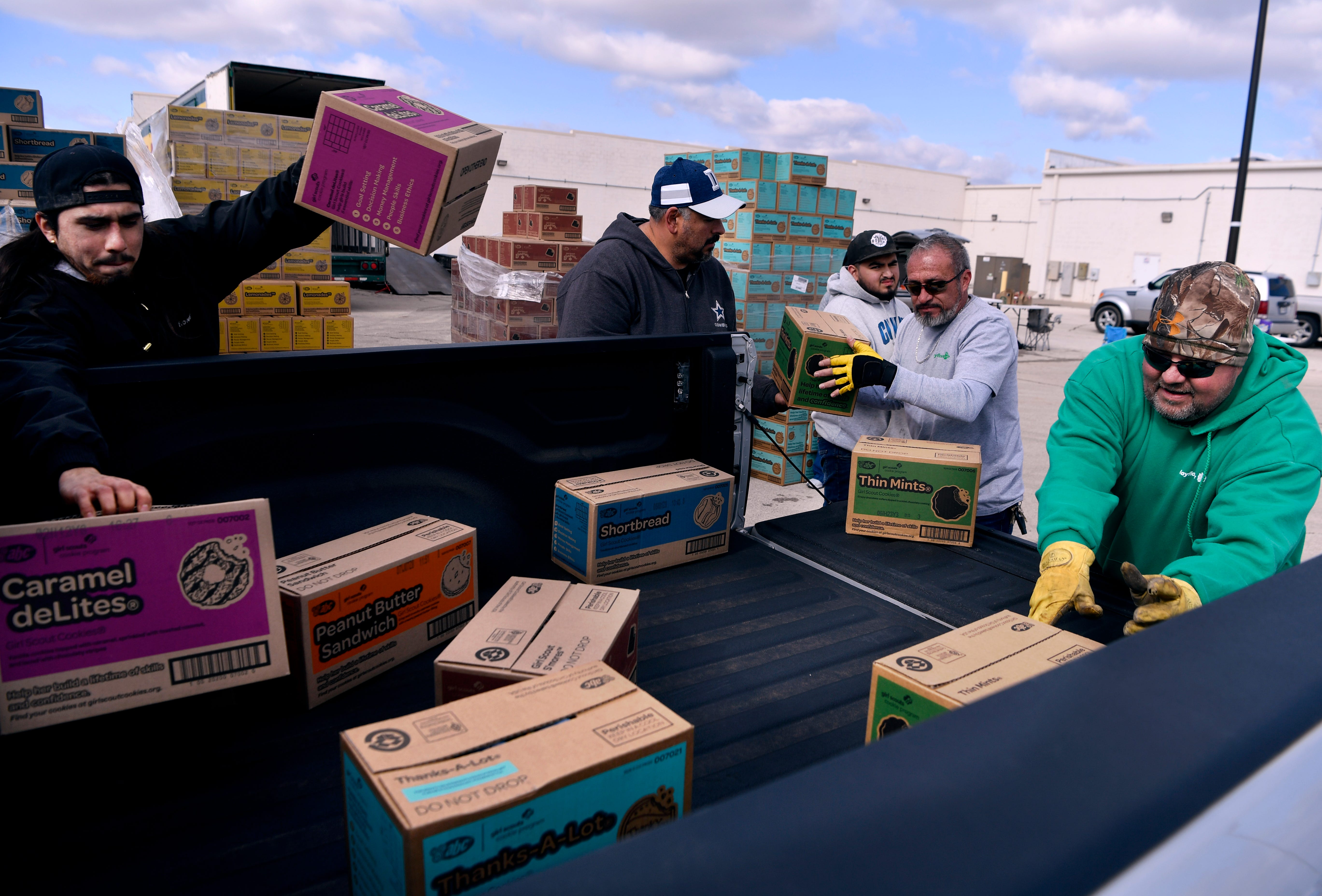 Men load Girl Scout cookies into the back of a waiting pickup Saturday. Cars lined up in the parking lot next to the Girl Scout office on Pioneer Drive, stretching more than 100 yards into the former K-Mart lot as families came to pick up their orders. Officials estimated they delivered approximately 77,800 cookies.