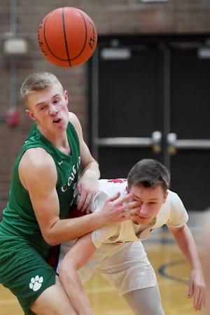 Mountain Heritage's Lucas Jenkins pokes Madison's Alex Chambers in the eye as they tussle for the ball Jan. 11, 2019 in Marshall. Mountain Heritage won, 84-57.