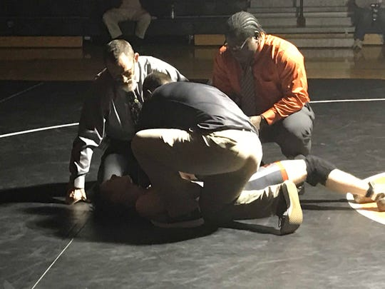 Trainers and coaches tend to Union-Endicott's Colby Bendick after he injured his shoulder in a 120-pound match against Vestal's Peter Sacco on Wednesday at U-E.