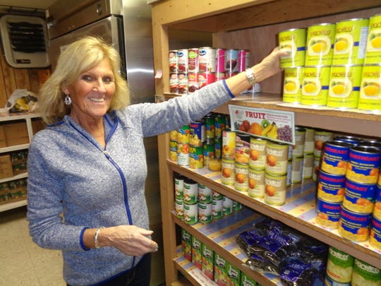 Pat Howe stacks cans inside Tioga County Rural Ministry's food pantry in Owego. Her favorite part of volunteering is interacting with the clients who seek help from the ministry.