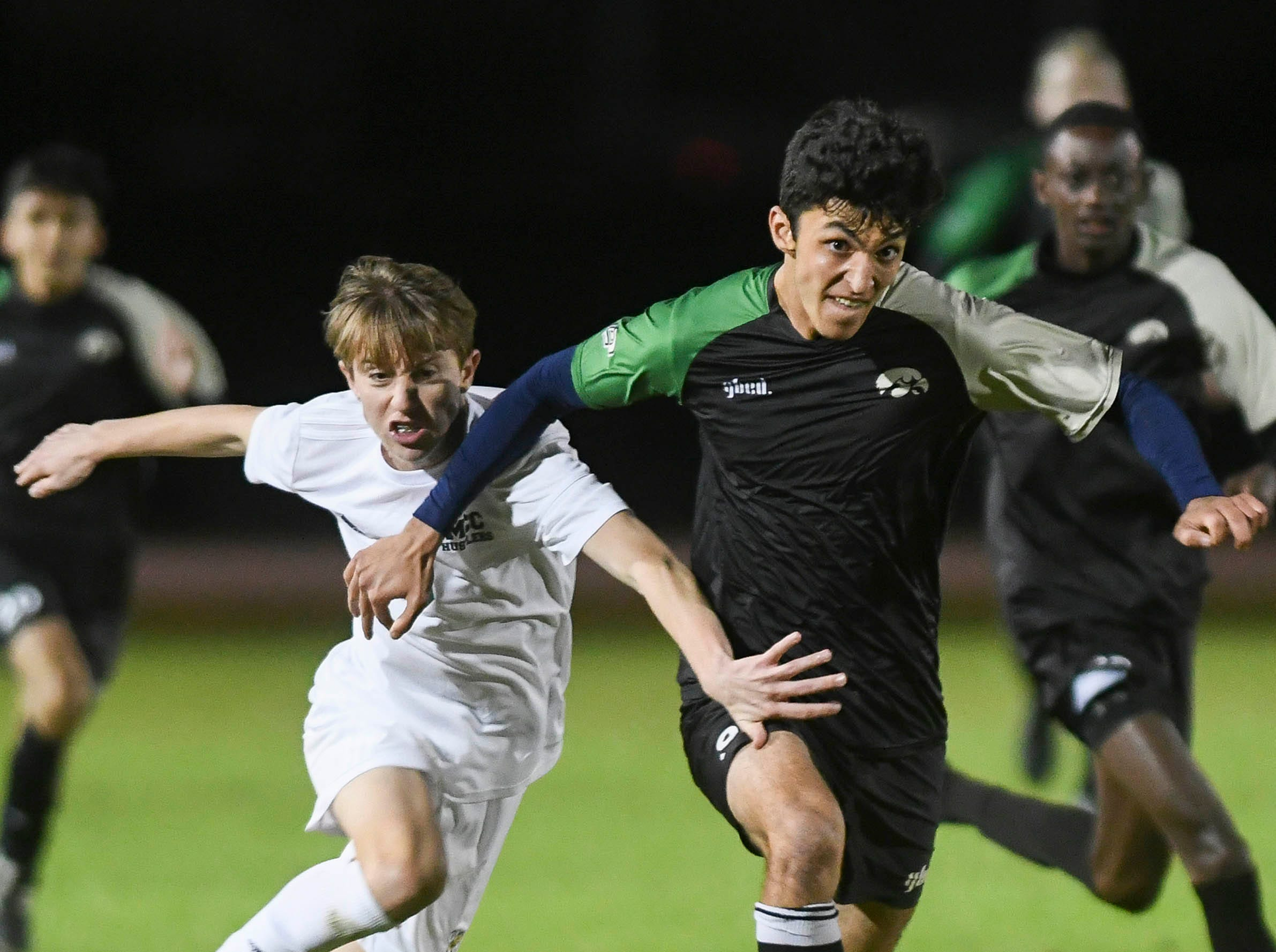 Seamus Wixted of Melbourne Central Catholic and Kia Mohajeri of Viera chase the ball during Friday's game in Viera