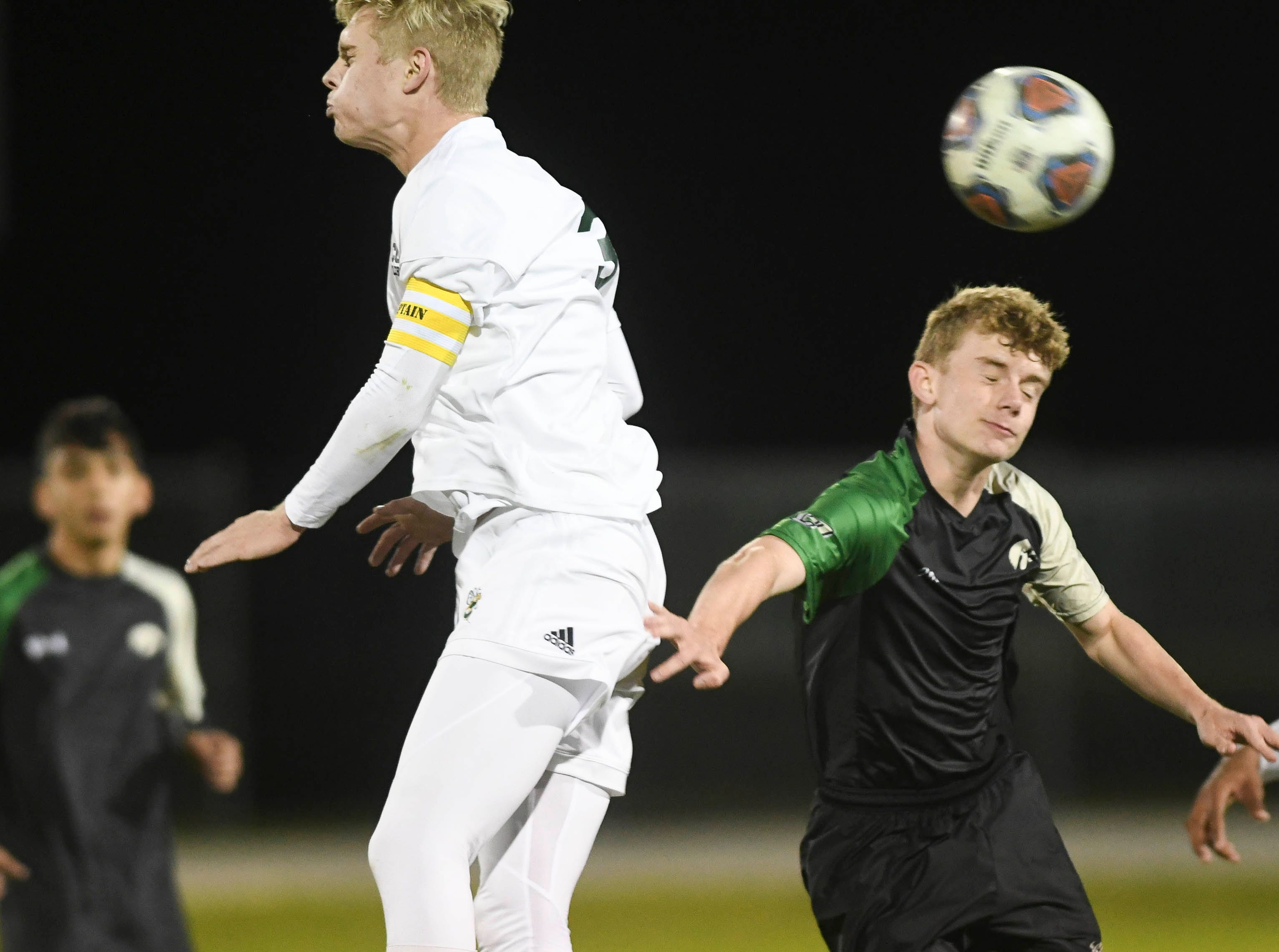 Tyler Keller of Melbourne Central Catholic heads the ball away from Zachary Nielsen of VIera during Friday's game in Viera.