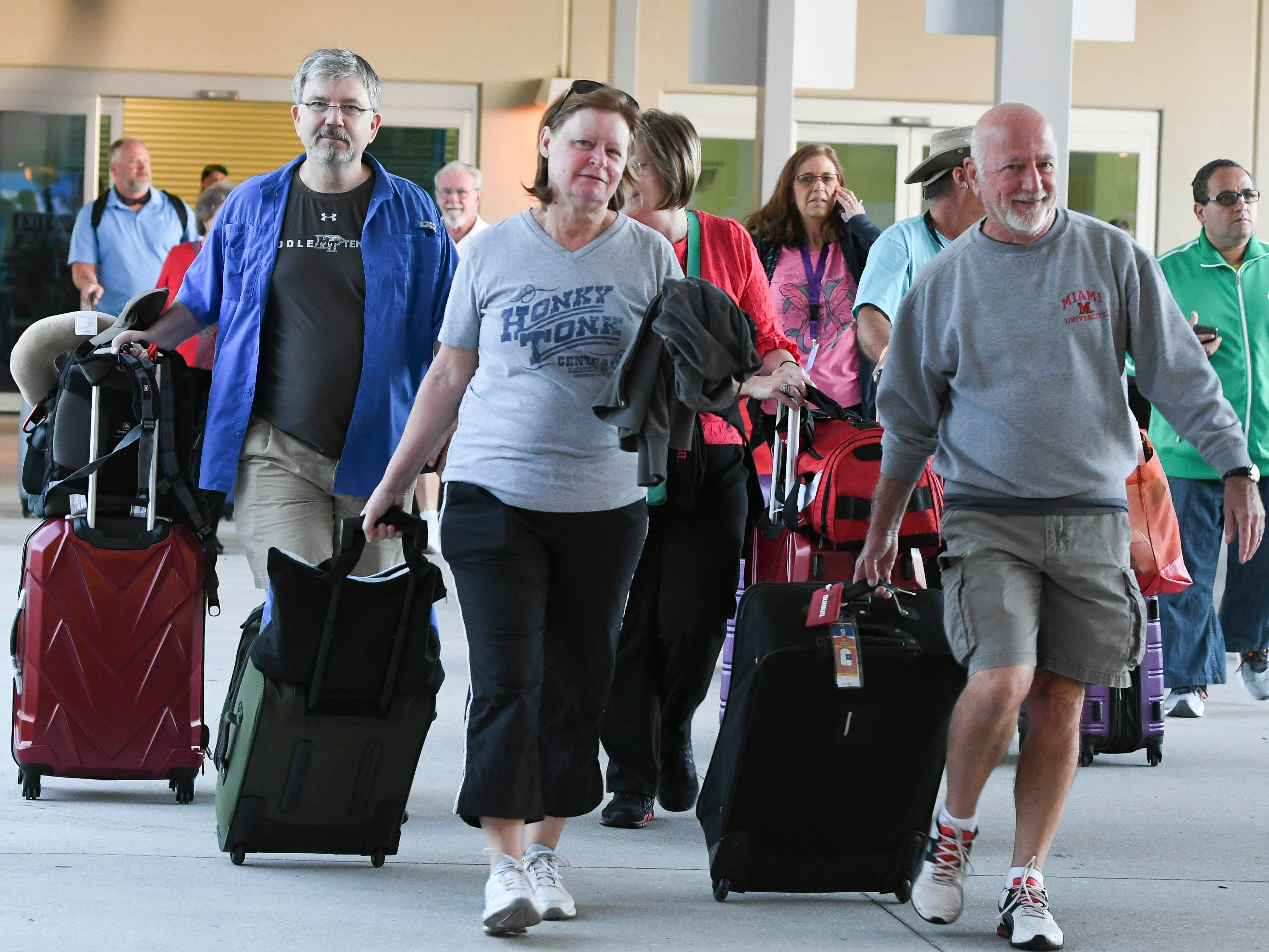 Passengers disembark from cruise ship Oasis of the Seas early Saturday morning at Port Canaveral.  The ship returned to port a day early due to an outbreak of Norovirus.