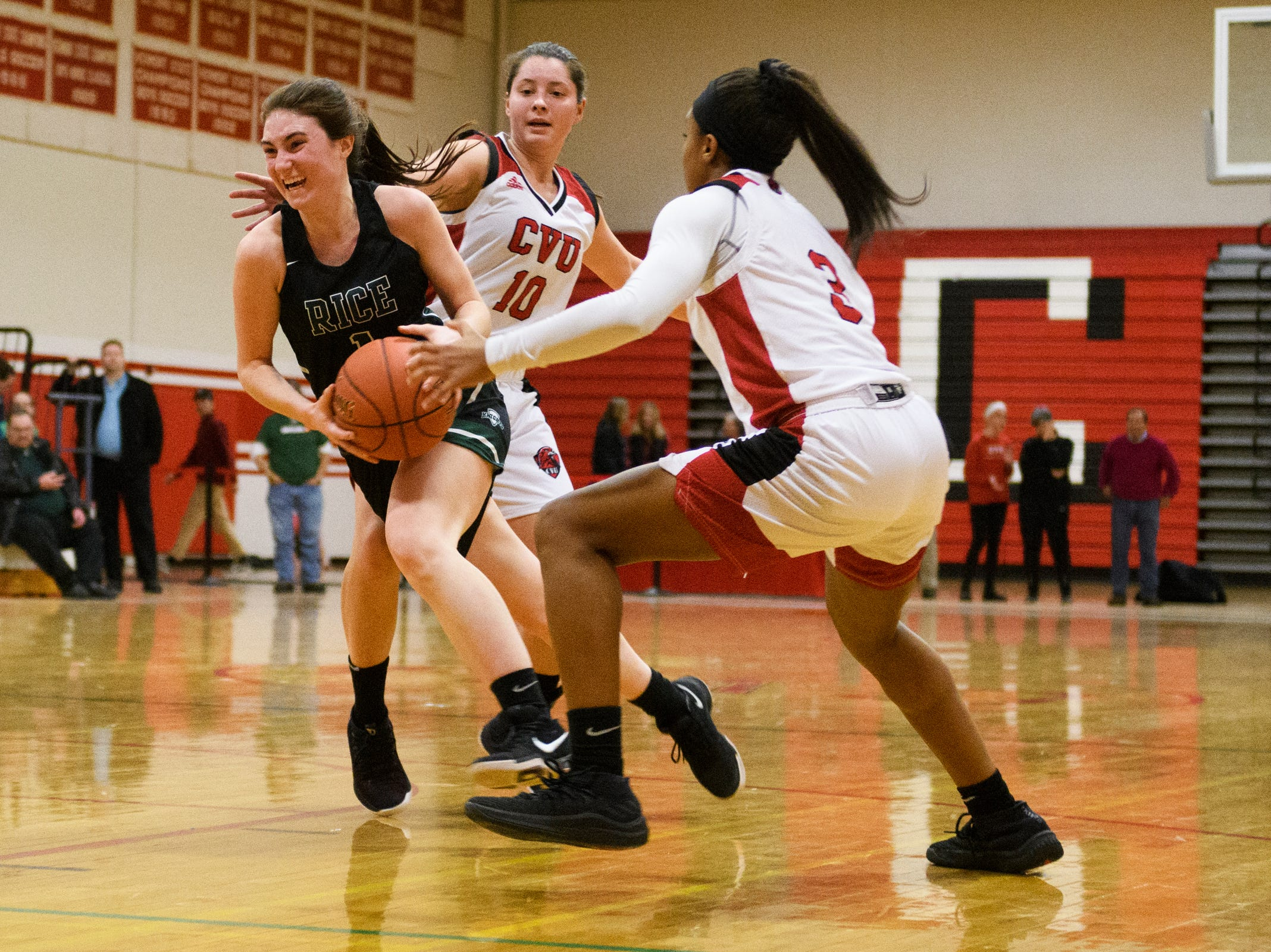 Rice's Kristen Varin (1) drives to the hoop past CVU's Makkena Boyd (3) and Quinn Boardman (10) during high school girls basketball game between the Rice Green Knights and the Champlain Valley Union Redhawks at CVU High School on Friday night January 11, 2019 in Hinesburg.
