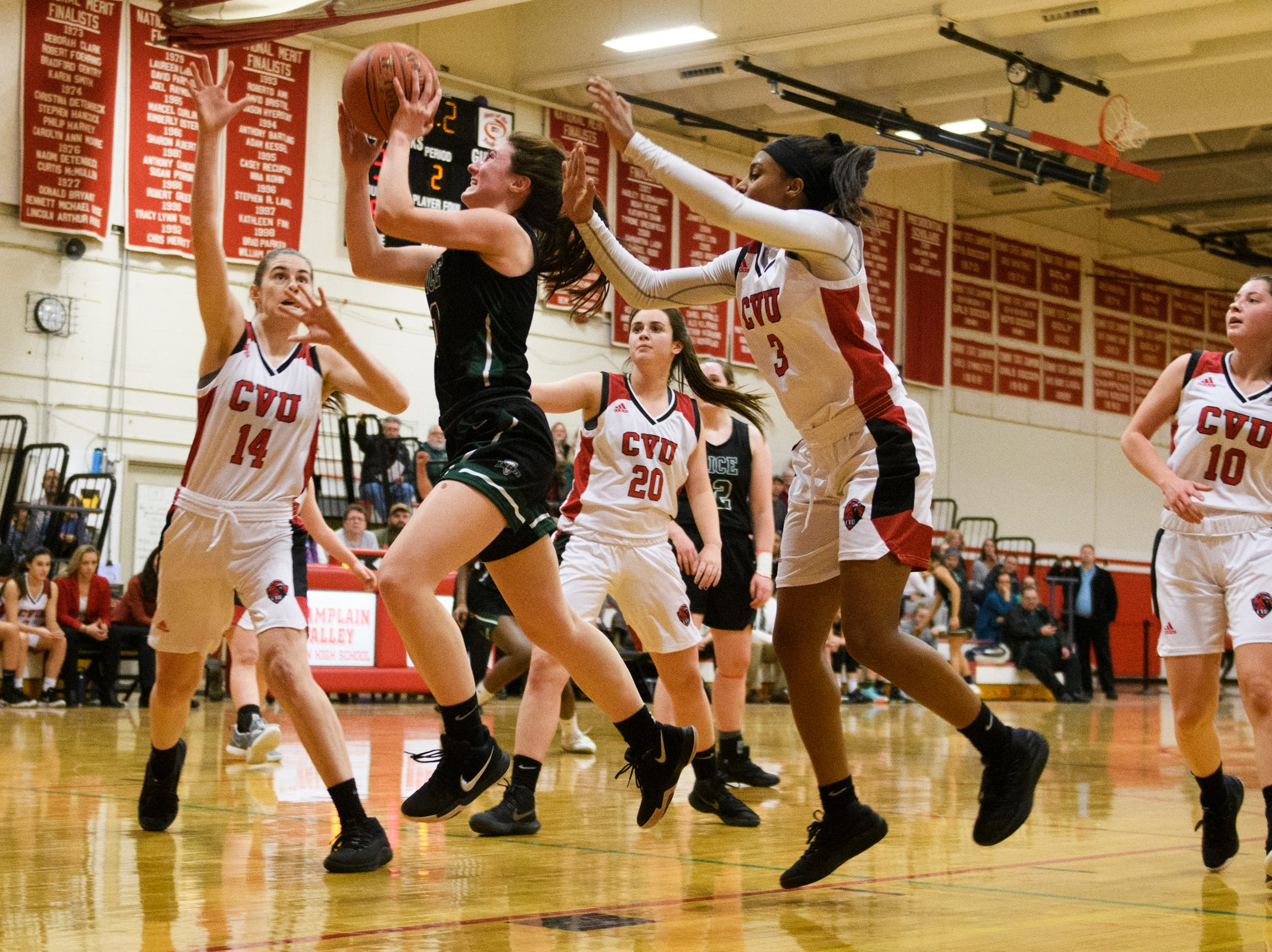 Rice's Kristen Varin (1) leaps for a lay up past CVU's Mekkena Boyd (3) and Julia Blanck (14) during high school girls basketball game between the Rice Green Knights and the Champlain Valley Union Redhawks at CVU High School on Friday night January 11, 2019 in Hinesburg.
