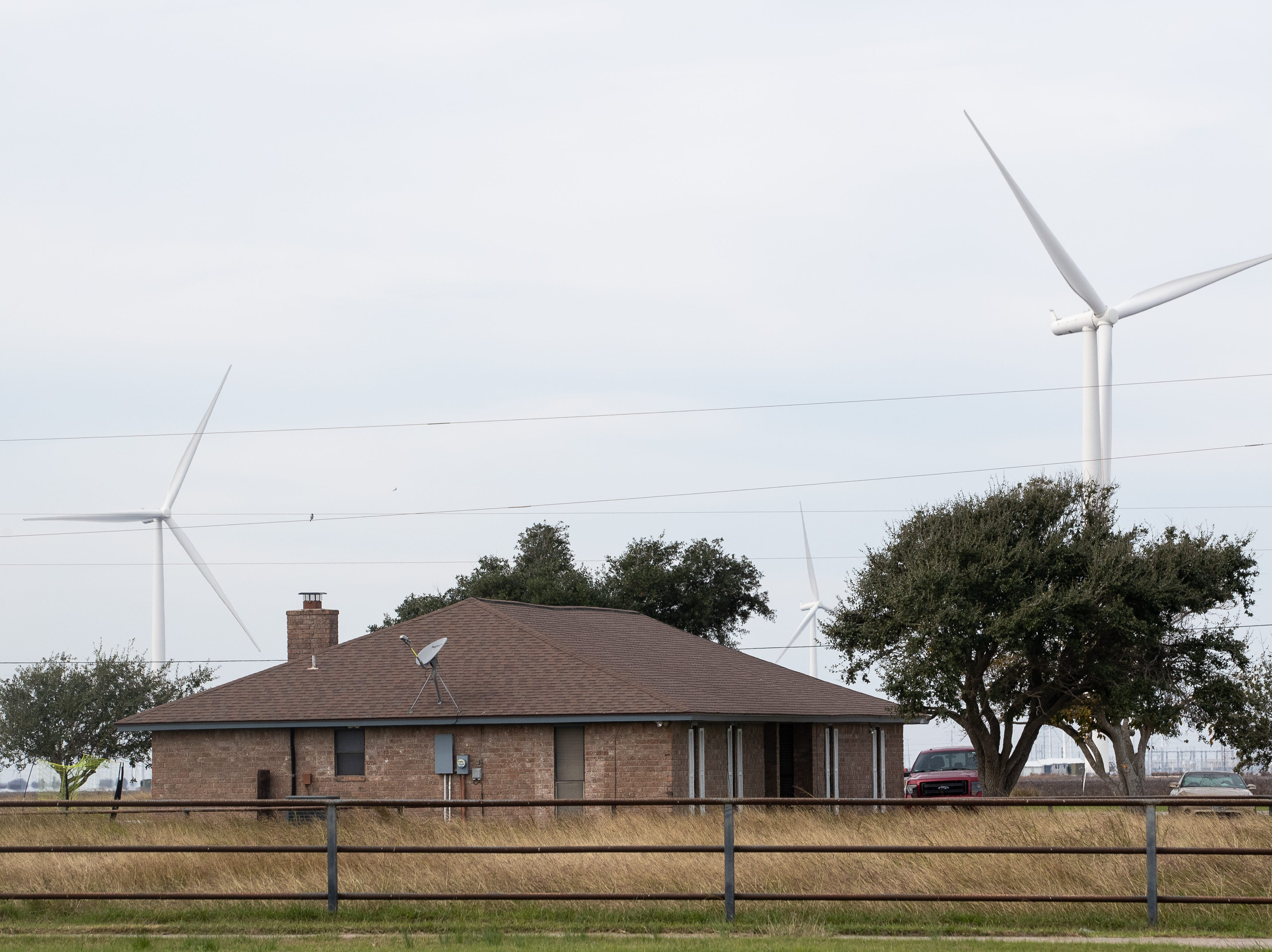 Wind turbines seen behind a home in San Patricio County near Portland, Texas.Texas is home to nearly four dozen manufacturing facilities and numerous component suppliers for wind energy.