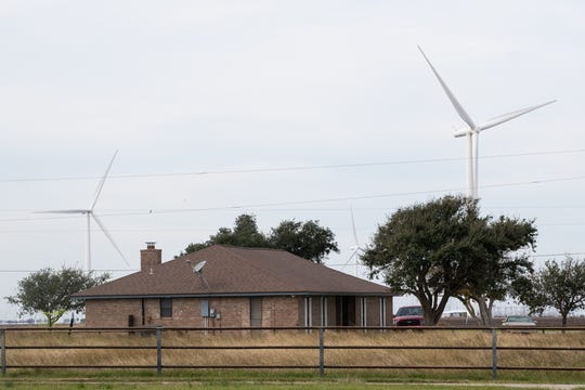 Wind turbines seen behind a home in San Patricio County near Portland, Texas. Texas is home to nearly four dozen manufacturing facilities and numerous component suppliers for wind energy.