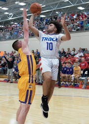 Zane Trace junior Cam Evans jumps over Unioto junior Jeremy Lambert to score Friday night at Zane Trace High School. Evans scored a total of 17 points for the night.