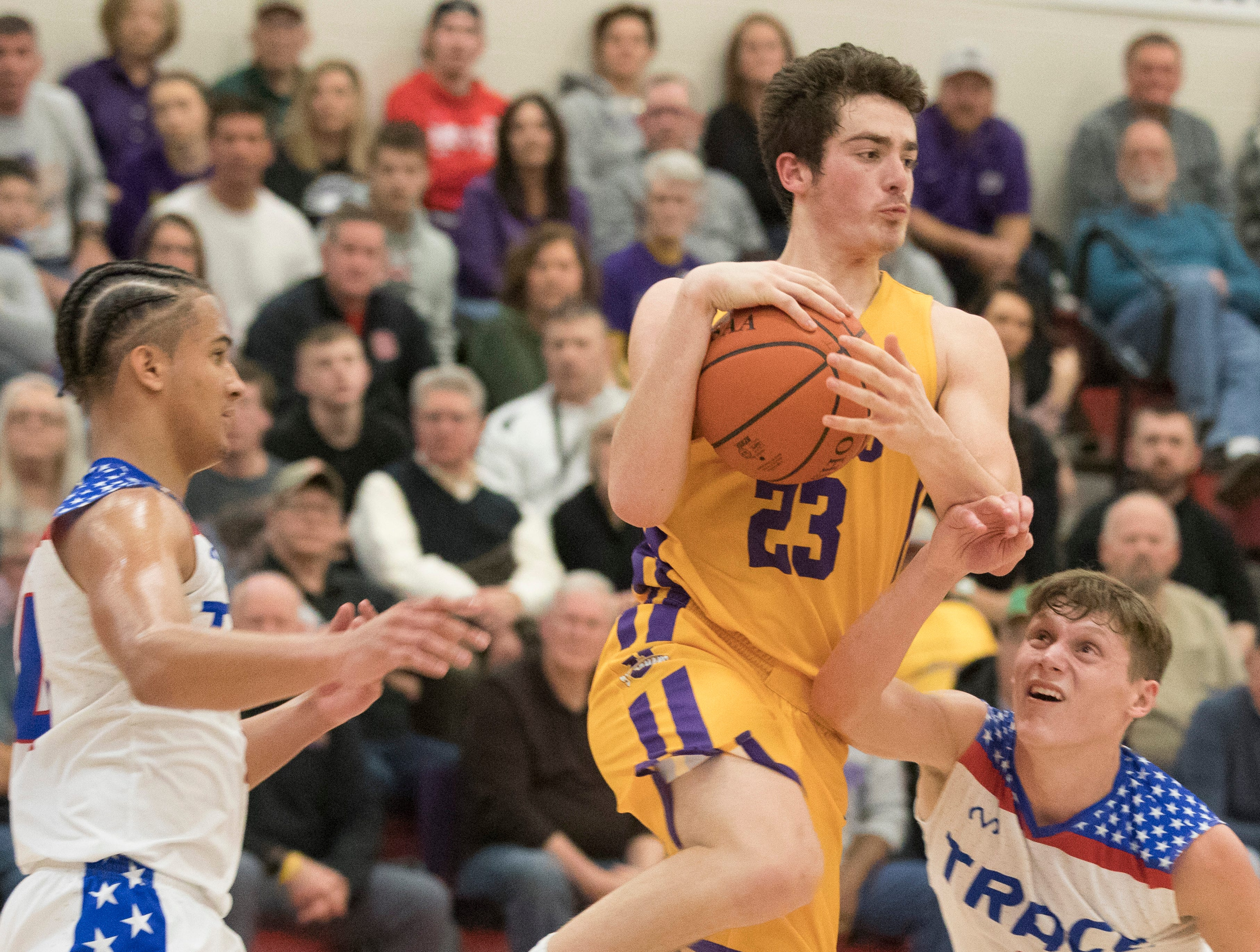 Unioto senior Gabe McBee looks for an opening to pass the ball as he jumps over Zane Trace's defense Friday night at Zane Trace High School.
