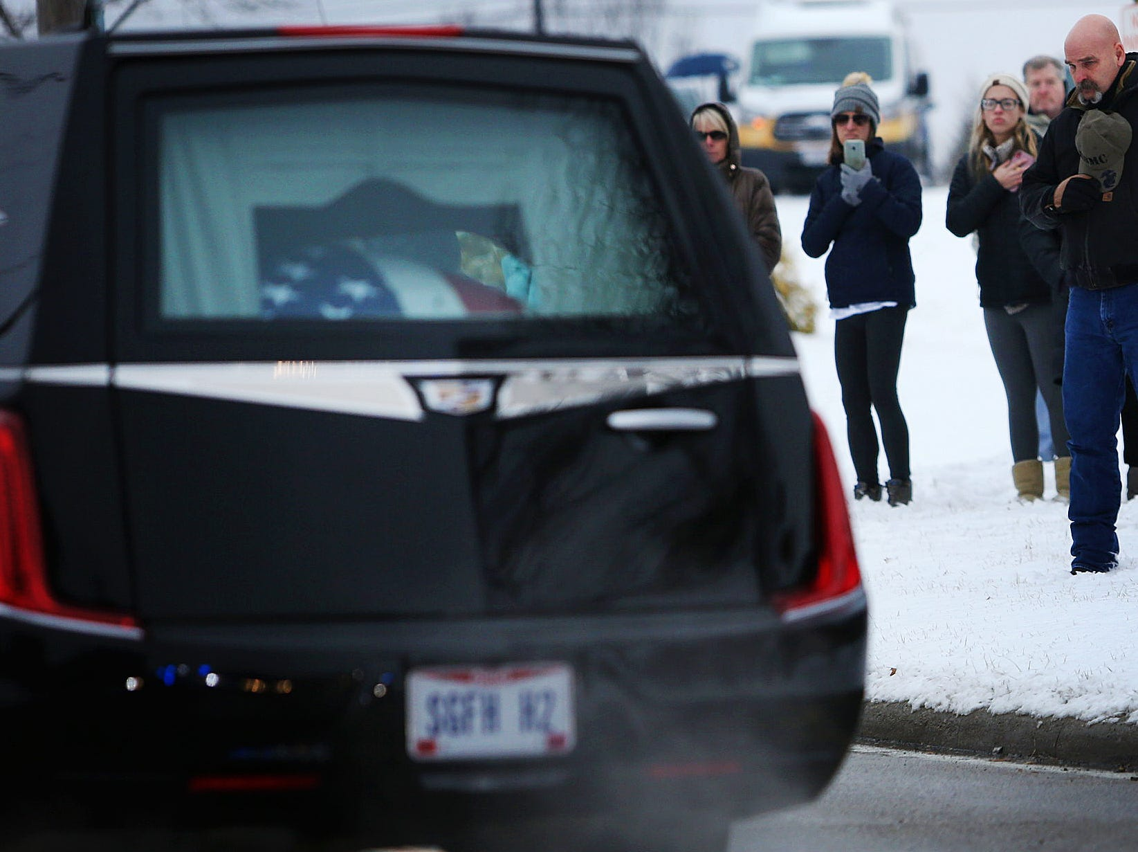 The hearse carrying Colerain Township Police Officer Dale Woods passes by the Colerain Community Center the Colerain Township Community Center, Saturday, Jan. 12, 2019. Woods, 46, who died Monday after being Hill by a pickup truck Jan. 4 while working at the scene of a crash.
