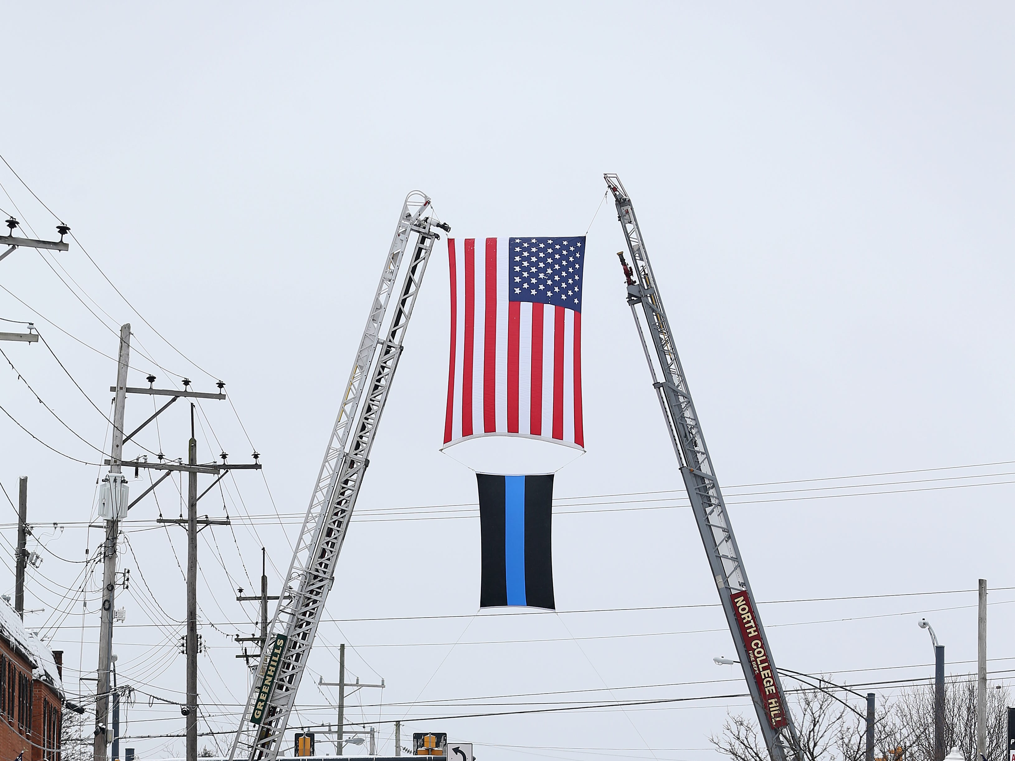 The procession for Colerain Township Police Officer Dale Woods passes through North College Hill along Galbraith Road, Saturday, Jan. 12, 2019, in North College Hill, Ohio. Woods, 46, who died Monday after being Hill by a pickup truck Jan. 4 while working at the scene of a crash.