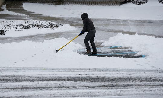 A man shovels as snow continues to fall on Colerain Aveune Saturday January 12, 2019. The National Weather Service cautioned that the accumulation will lead to hazardous travel in the area, recommending travelers stay home if possible until Sunday.