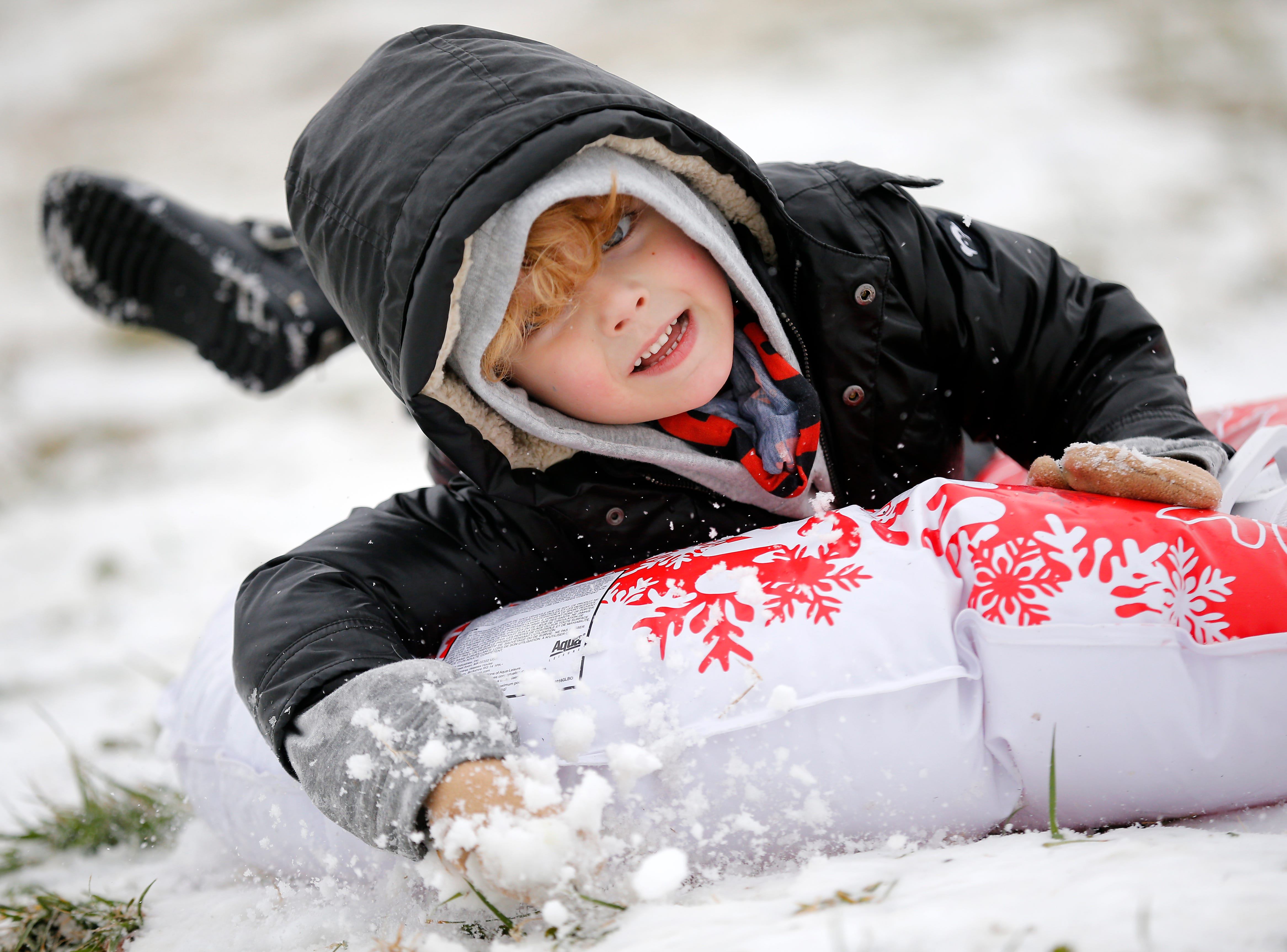 Wolfgang Steinke, 6, of Mt. Lookout smiles as he sleds downhill at Ault Park in the Hyde Park neighborhood of Cincinnati on Saturday, Jan. 12, 2019. A winter storm warning remained in effect until 7 a.m. Sunday after the region experienced the first snowfall of 2019.
