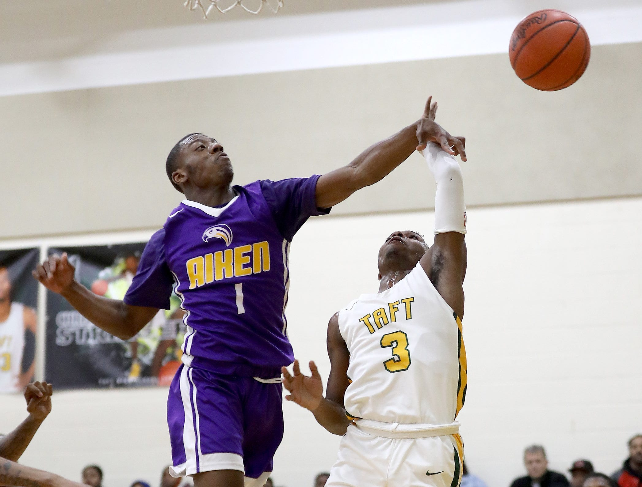 Taft guard Demarco Bradley has his shot blocked by Aiken guard D'Arris Dean.