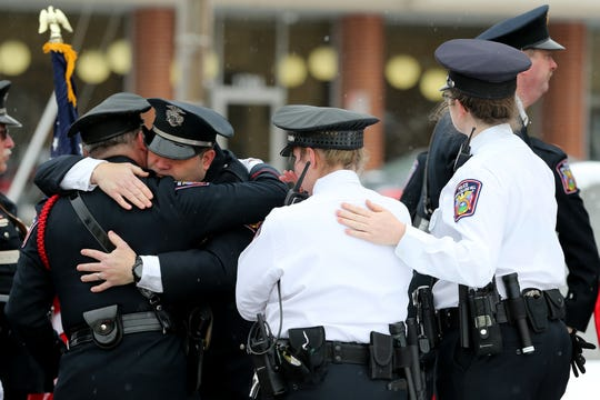 Members of the North College Hill Police Department embrace following the procession for Colerain Township Police Officer Dale Woods passing through North College Hill along Galbraith Road, Saturday, Jan. 12, 2019, in North College Hill, Ohio. Woods, 46, who died Monday after being Hill by a pickup truck Jan. 4 while working at the scene of a crash.
