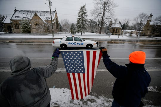 Marianne Shelton and her husband Jim Shelton, of Northside, holds an American flag at the beginning of a procession for fallen Colerain Police officer Dale Woods outside Spring Grove Cemetery in the Northside neighborhood of Cincinnati on Saturday, Jan. 12, 2019.