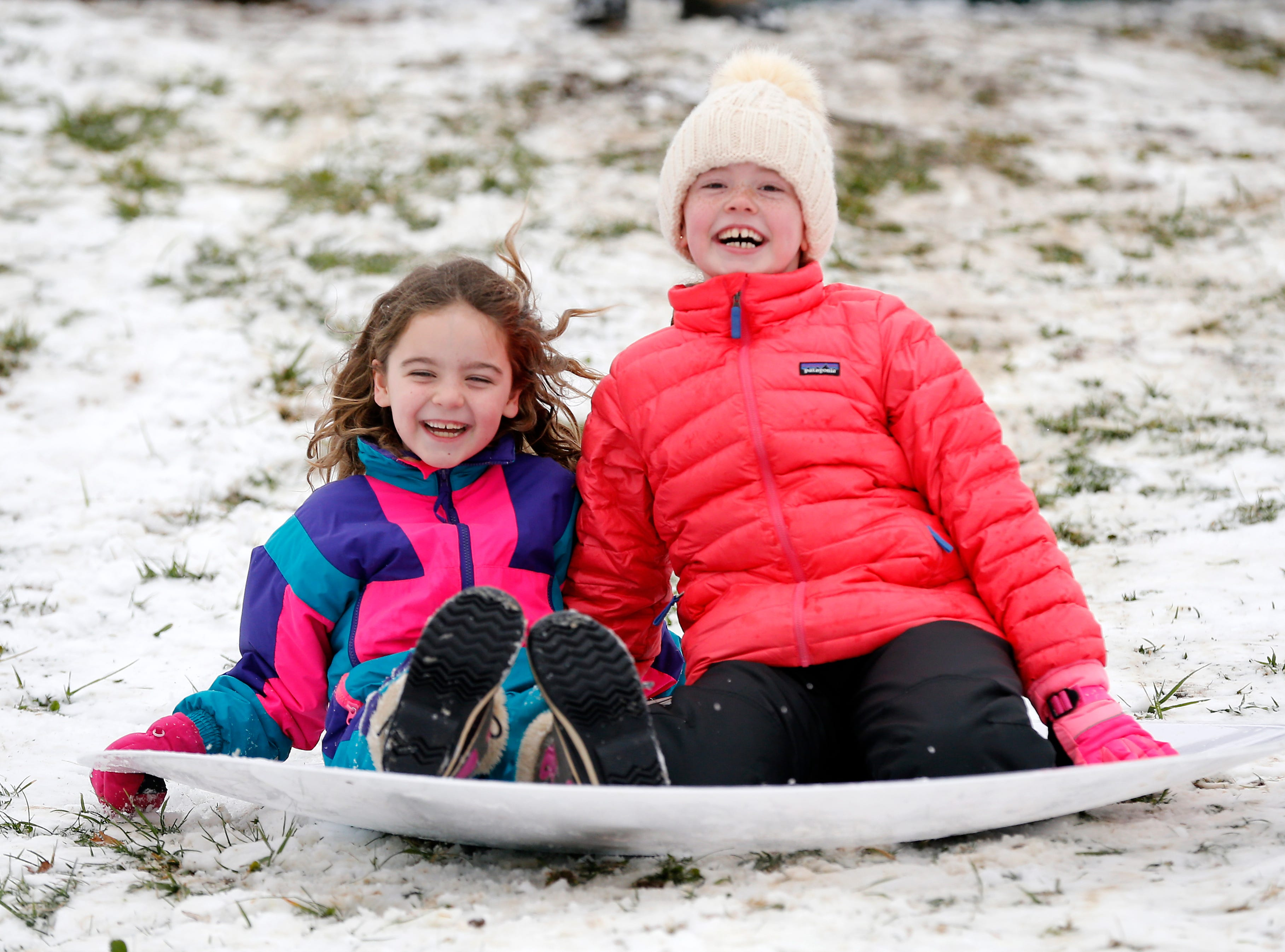 Sisters Becca, 7, and Blair Ryan, 9, of Columbia Tusculum, ride downhill together at Ault Park in the Hyde Park neighborhood of Cincinnati on Saturday, Jan. 12, 2019. A winter storm warning remained in effect until 7 a.m. Sunday after the region experienced the first snowfall of 2019.