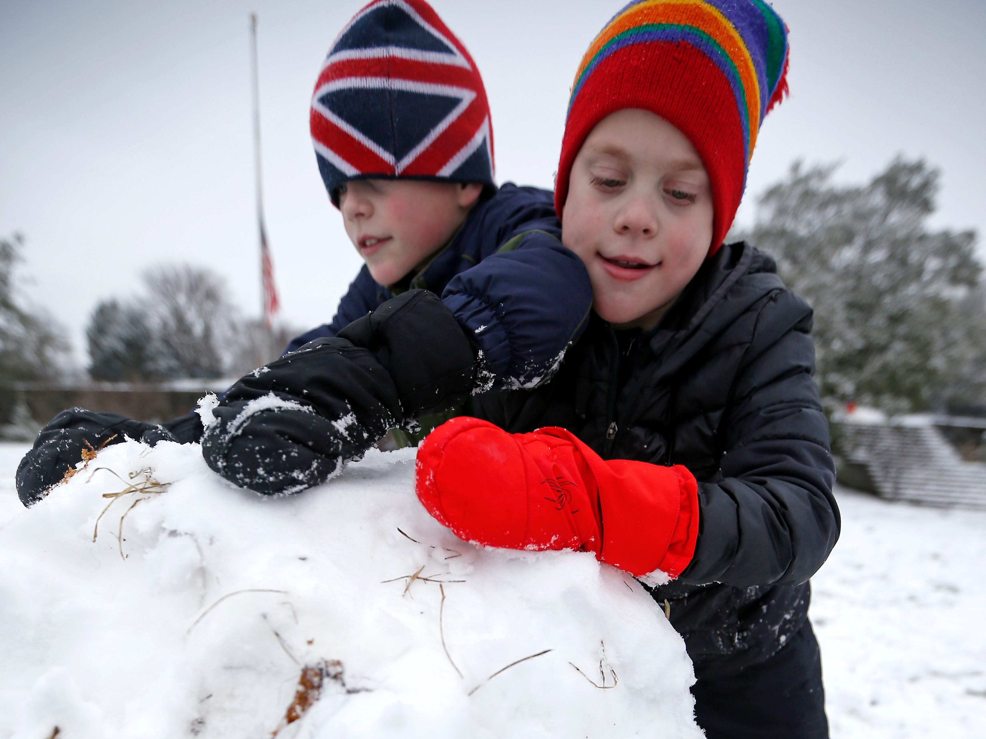 Twin brothers Bret and CJ Gash, 8, of Mt. Lookout roll the bottom section of a snowman at Ault Park in the Hyde Park neighborhood of Cincinnati on Saturday, Jan. 12, 2019. A winter storm warning remained in effect until 7 a.m. Sunday after the region experienced the first snowfall of 2019.