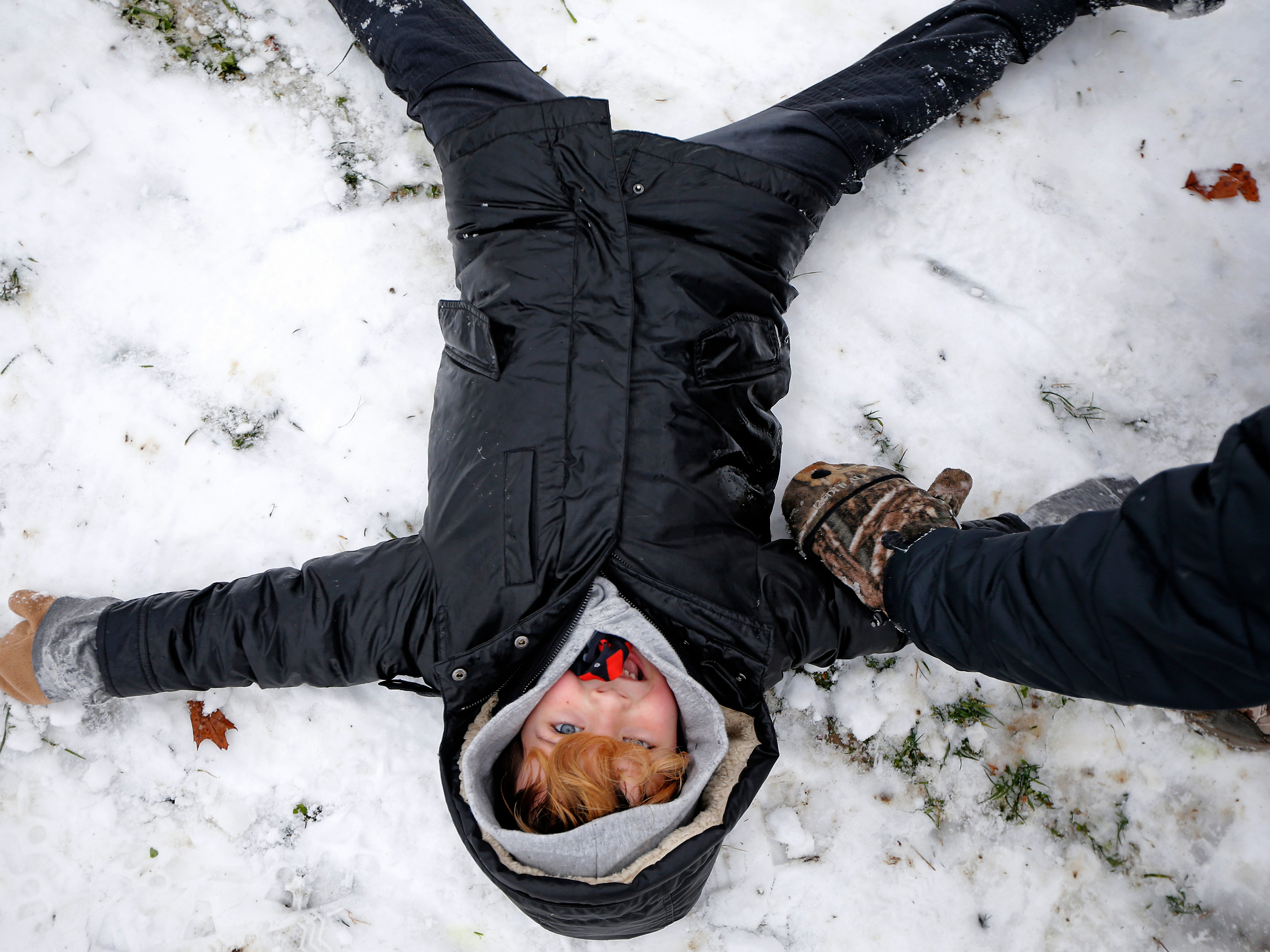 Wolfgang Steinke, 6, of Mt. Lookout, giggles and creates a snow angel as his dad, Adam Steike, attempts to pick him up at the bottom of the sledding hill at Ault Park in the Hyde Park neighborhood of Cincinnati on Saturday, Jan. 12, 2019. A winter storm warning remained in effect until 7 a.m. Sunday after the region experienced the first snowfall of 2019.