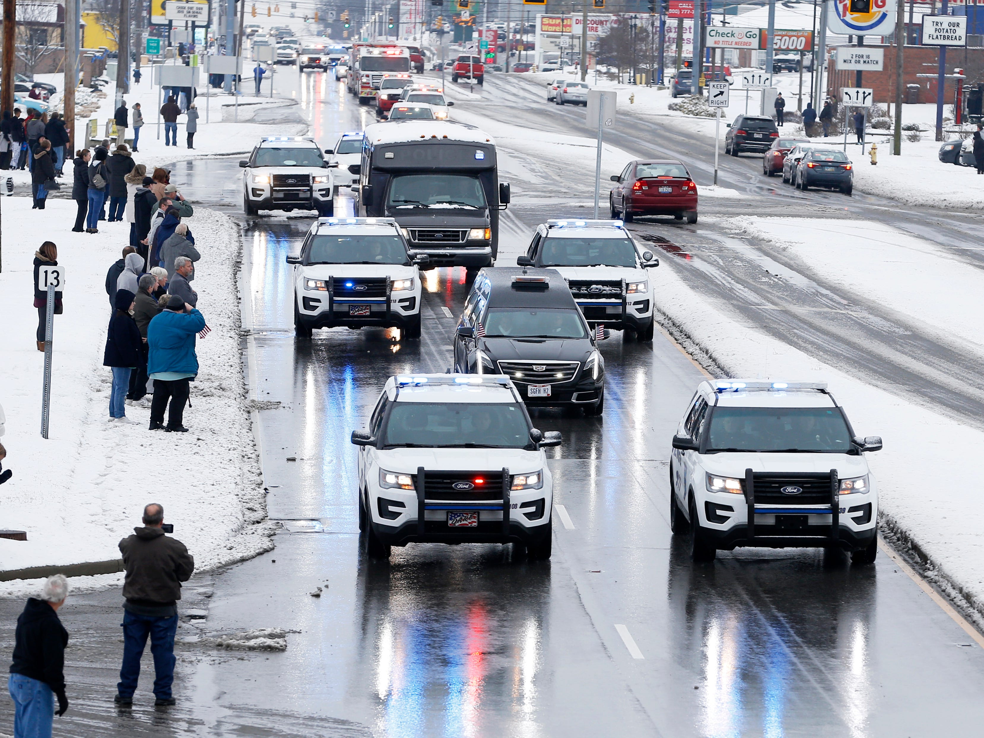 The funeral procession for Colerain Police Officer Dale Woods travels north on Colerain Avenue Saturday January 12, 2019. Dale Woods, 46, died Monday after being hit by a pickup truck Jan. 4 while working at the scene of a crash.