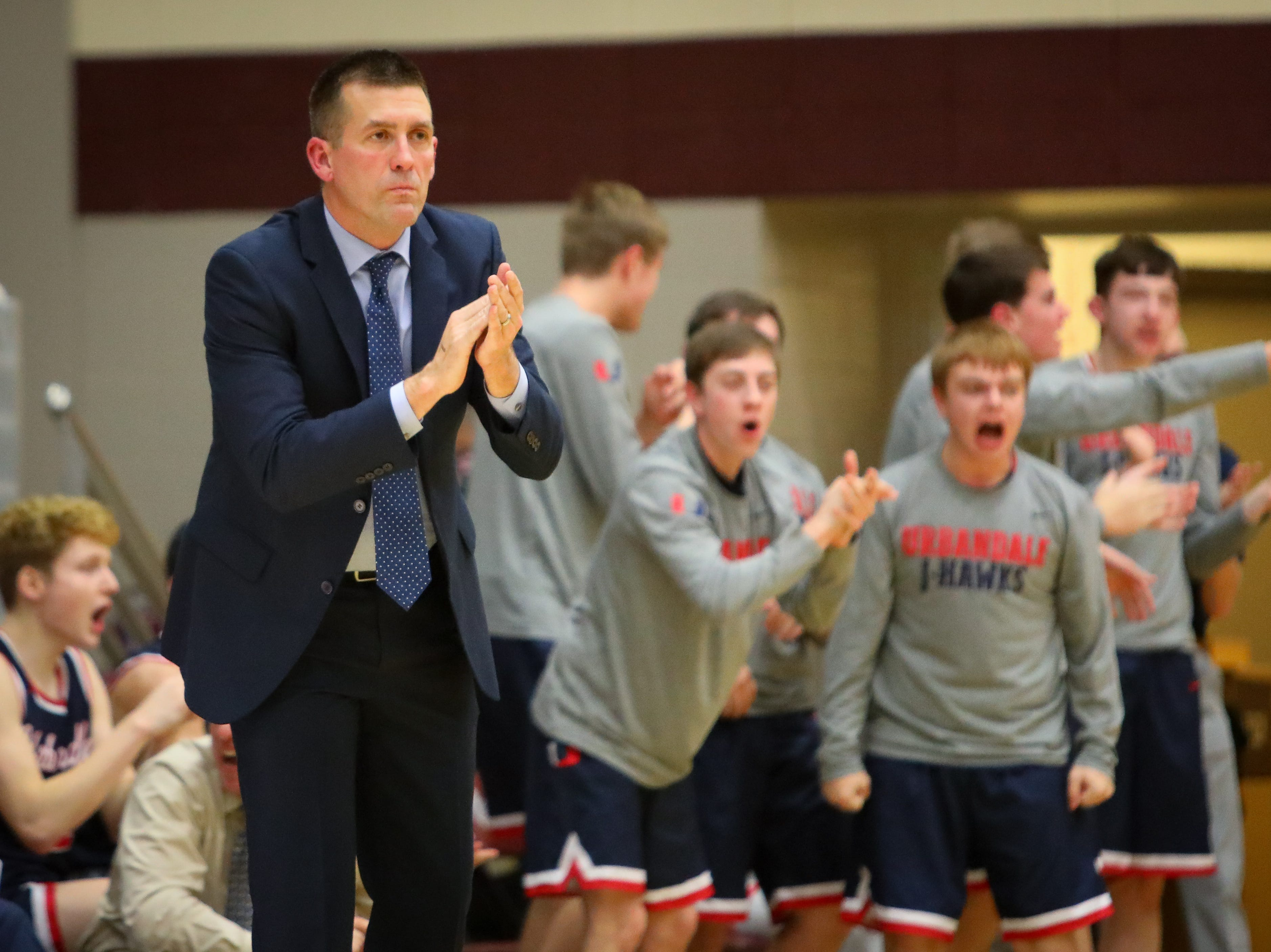 Urbandale head coach Jon Schmitz celebrates after a play during a boys high school basketball game between the Urbandale J-Hawks and the Dowling Catholic Maroons at Dowling Catholic High School on Jan. 11, 2019 in West Des Moines, Iowa.
