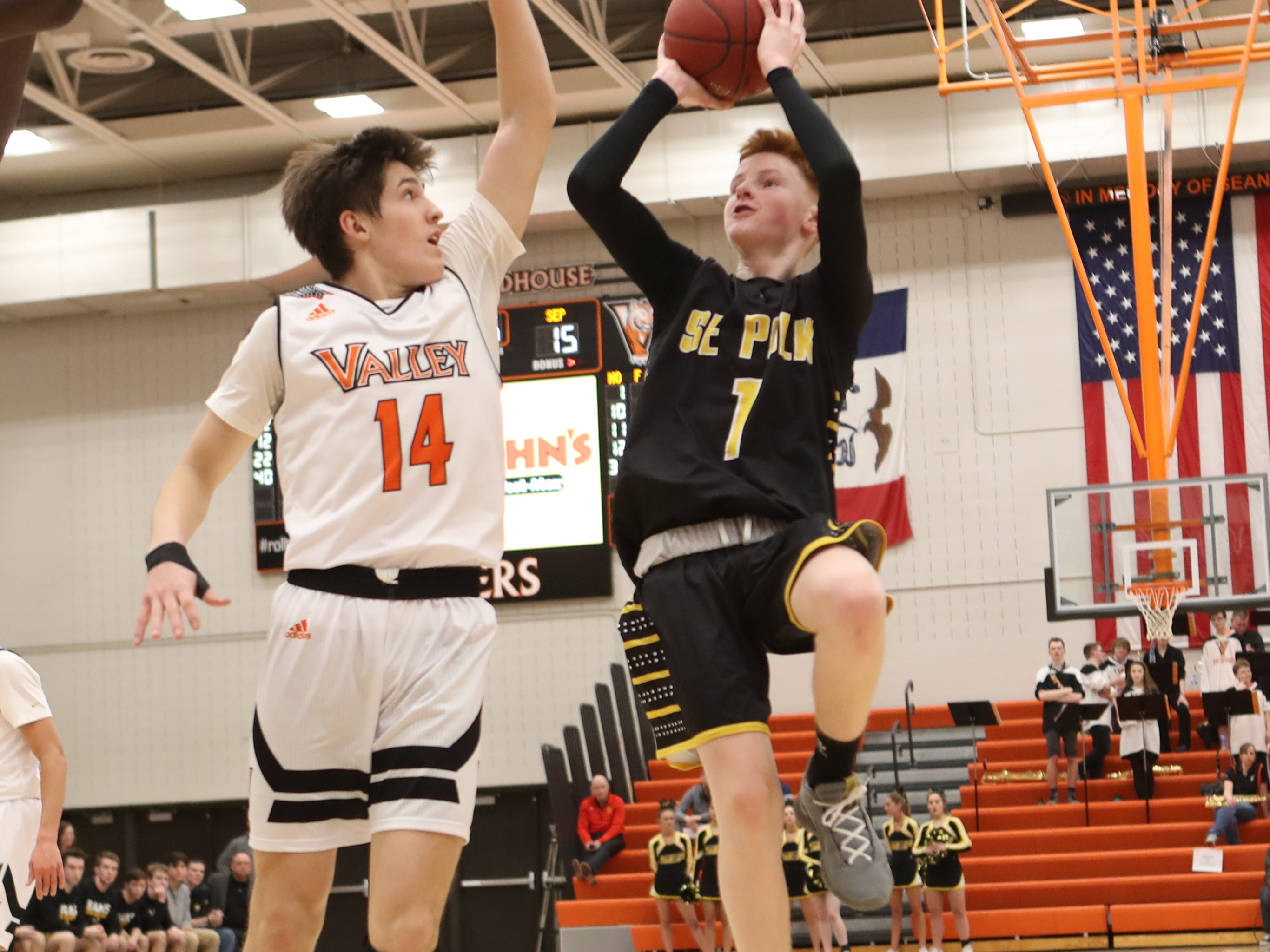 Southeast Polk Rams' James Glenn (1) is defended by Valley Tigers' Jake Auer (14) during a boys basketball game at Valley High School on Jan. 11, 2019.