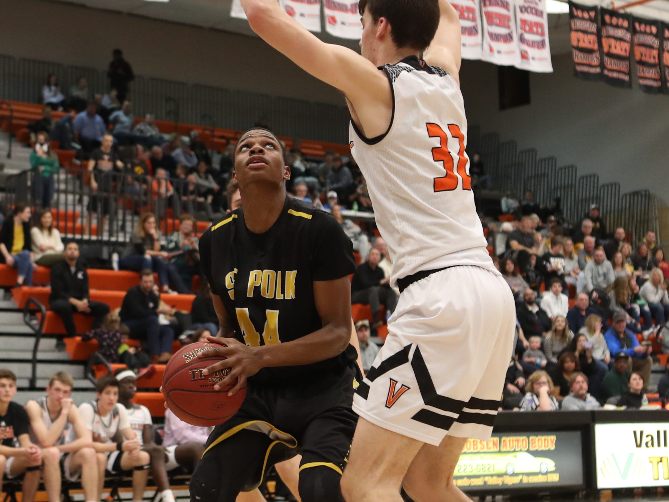 Valley Tigers' Will Berg (32) defends the shot of Southeast Polk Rams' Malichai Williams (44) during a boys basketball game at Valley High School on Jan. 11, 2019.