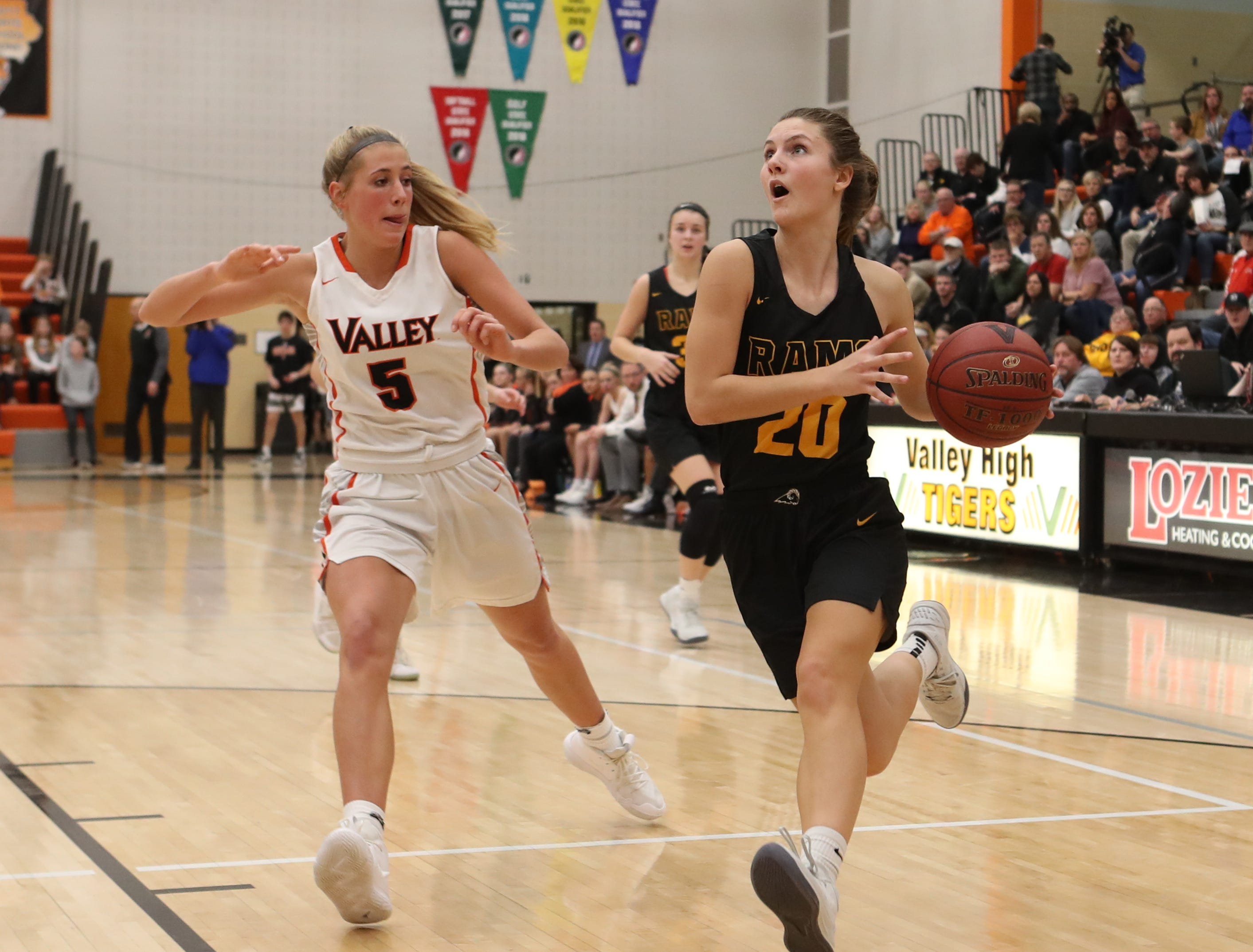 Southeast Polk Rams' Sami Albertson (20) drives past Valley Tigers' Grace Plummer during a girls basketball game at Valley High School on Jan. 11, 2019.