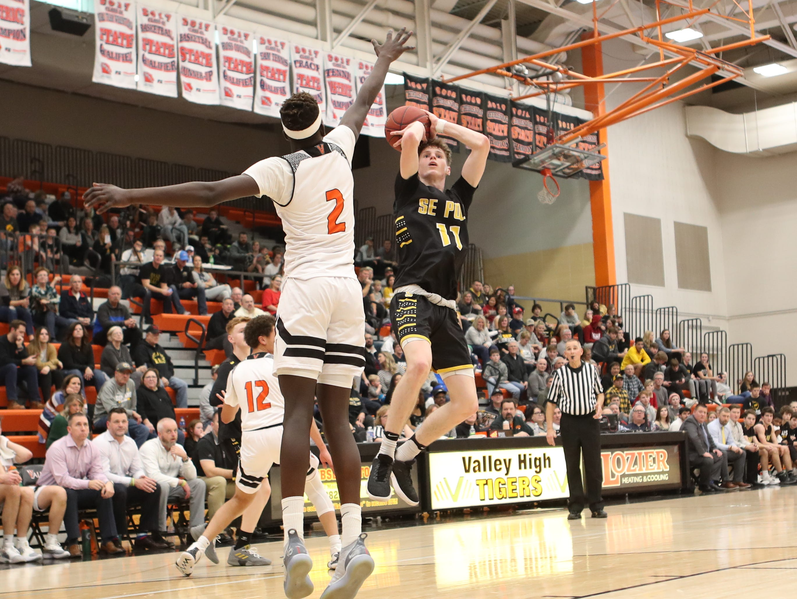 Southeast Polk Rams' Sam Glenn (11) shoots over Valley Tigers' Aguek Deng during a boys basketball game at Valley High School on Jan. 11, 2019. Valley won, 61-54.