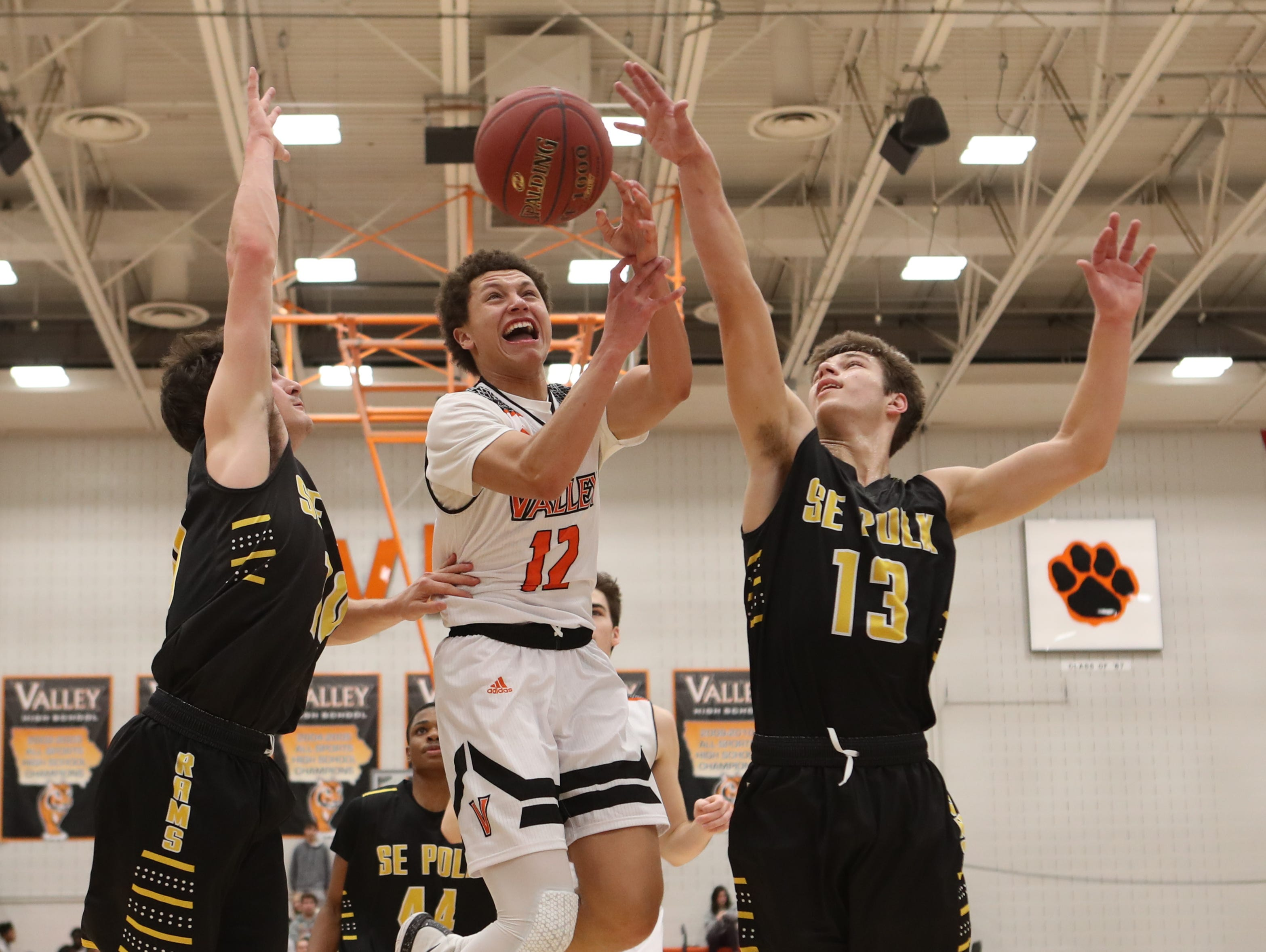 Southeast Polk Rams' Dominic Caggiano (13) blocks the shot from Valley Tigers' Evan Obia (12) during a boys basketball game at Valley High School on Jan. 11, 2019.