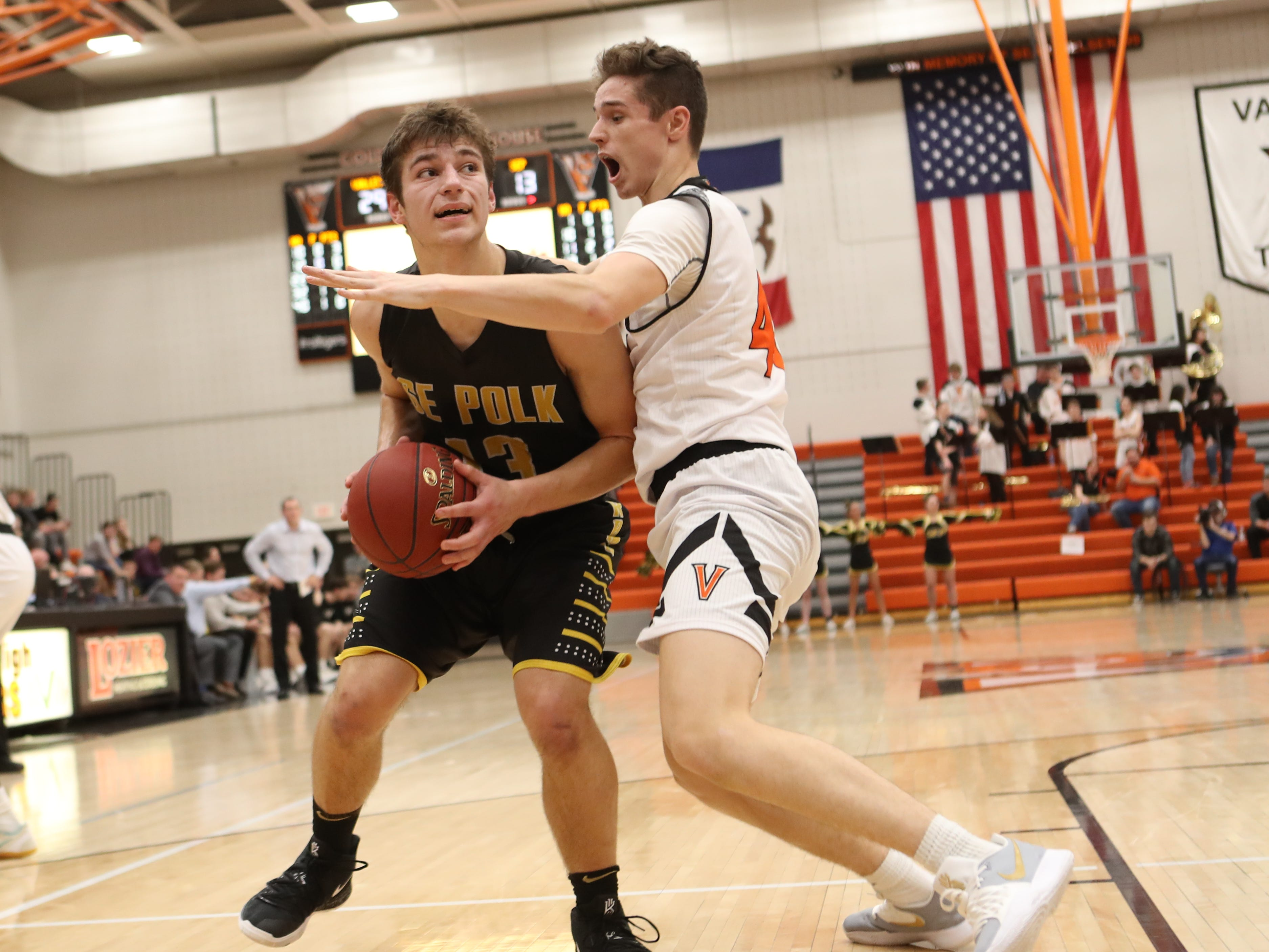 Valley Tigers' Michael Chambers (42) defends Southeast Polk Rams' Dominic Caggiano (13) during a boys basketball game at Valley High School on Jan. 11, 2019.